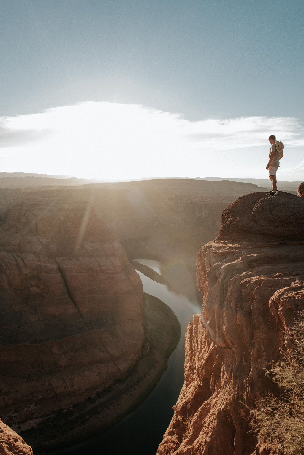 Hiker taking in view at Horseshoe Bend at sunset