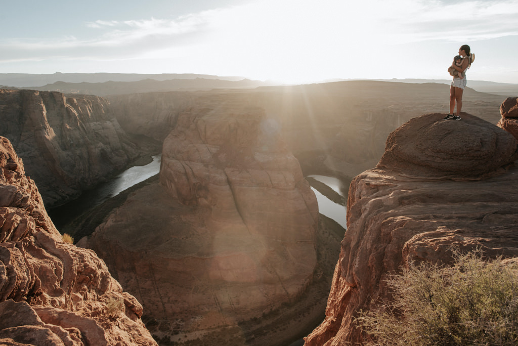 Mother with son in infant carrier taking in view of Horseshoe Bend at sunset