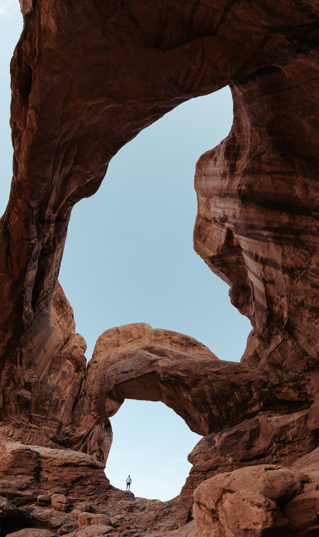 Man standing under Double Arch at Arches National Park