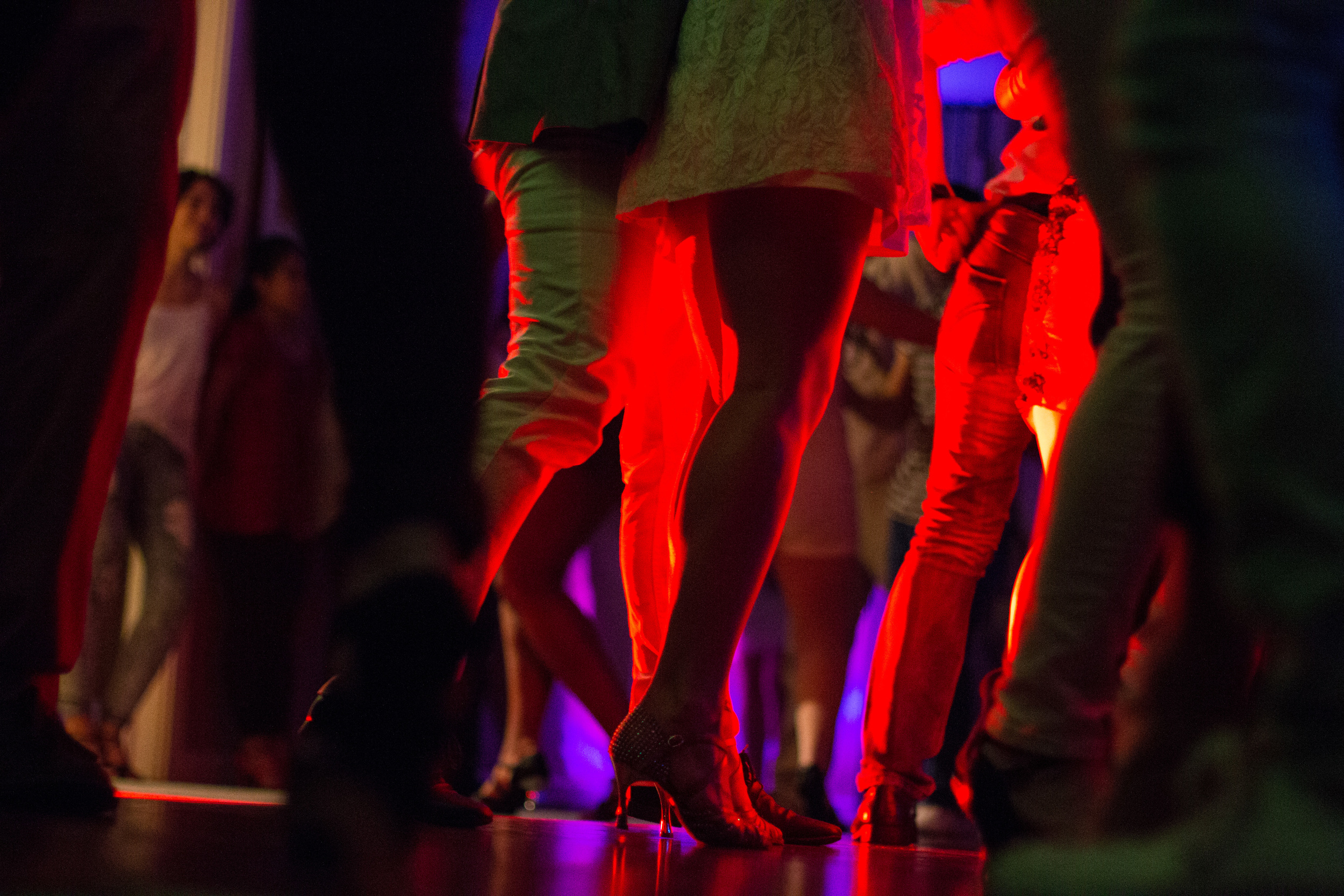 In the bachata room, couples crowd closely on the dance floor: women in their high heels and men in flat shoes.