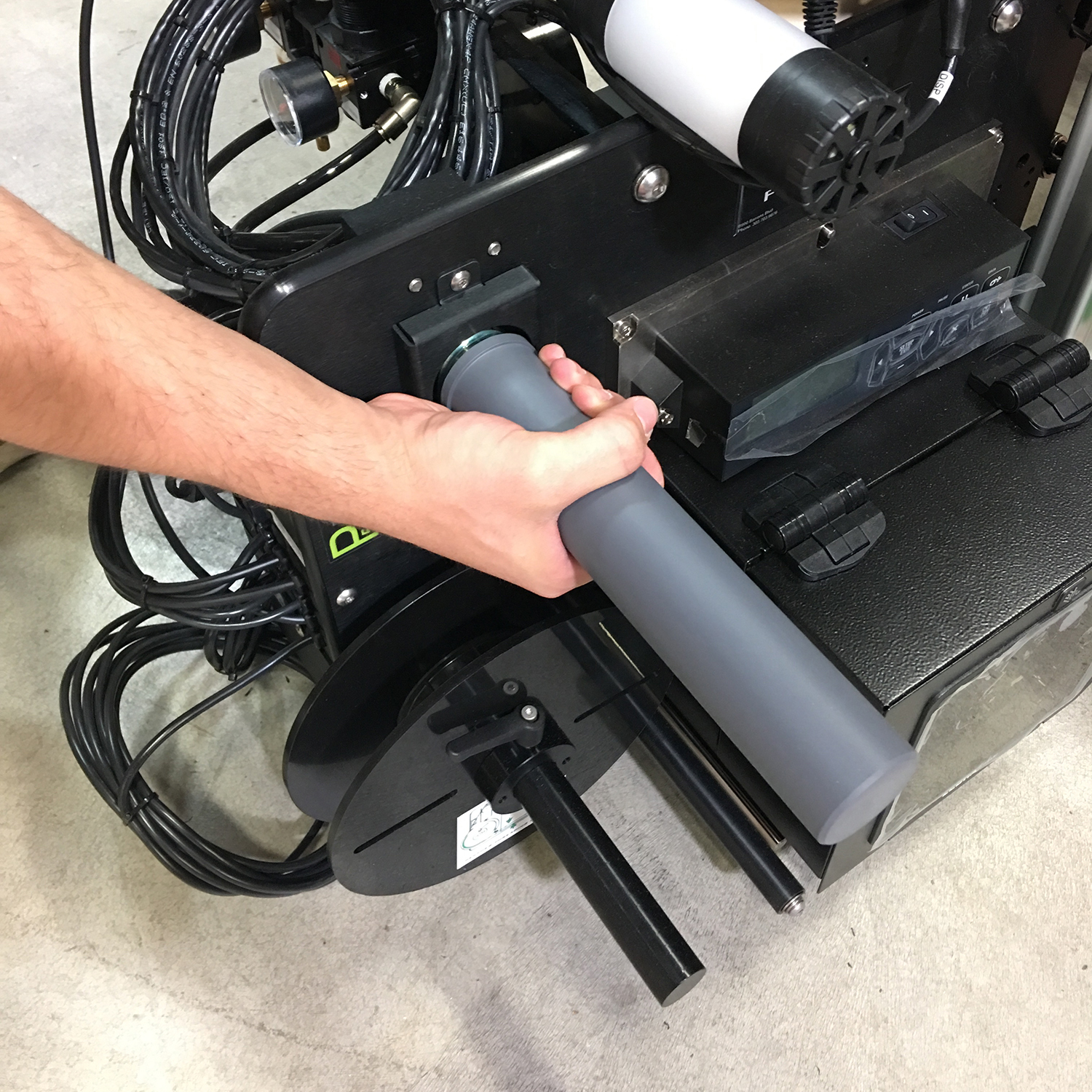 Lift from under the gray waste take-up roller. The location of the roller on your specific system may be in a different position than shown above.