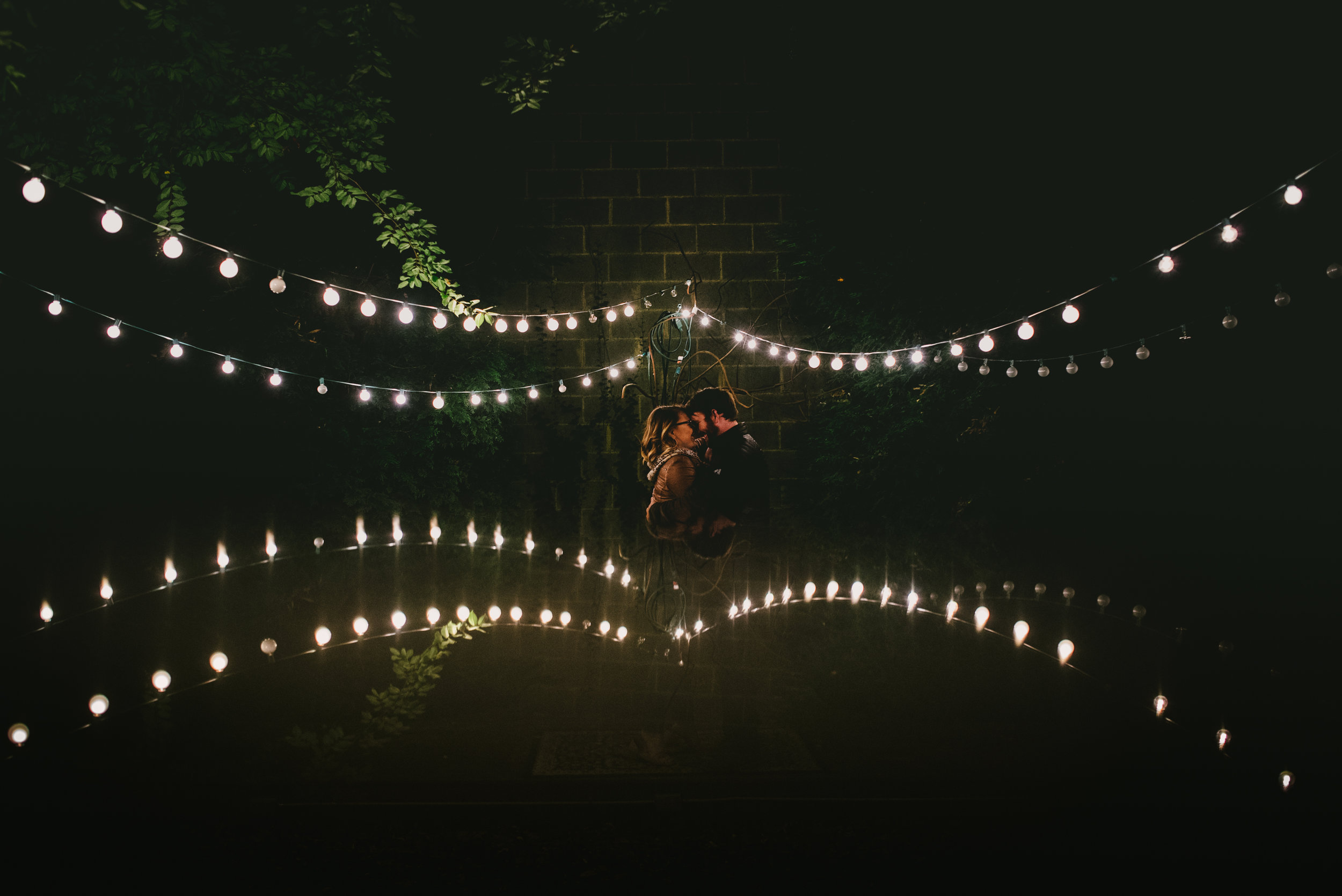 enchanted garden inspired engagement photo on the terrace of Lindley Park Filling Station, Greensboro, North Carolina