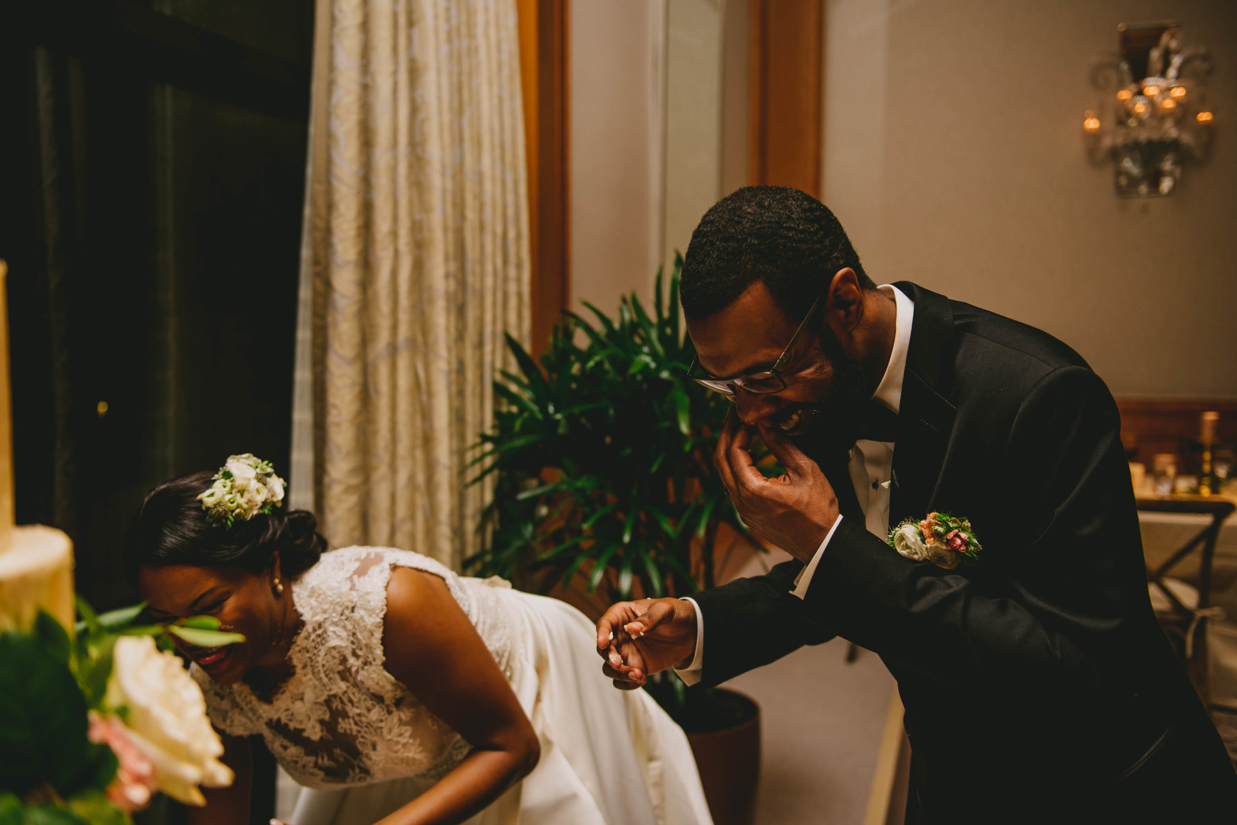 The bride and groom clean cake off their faces