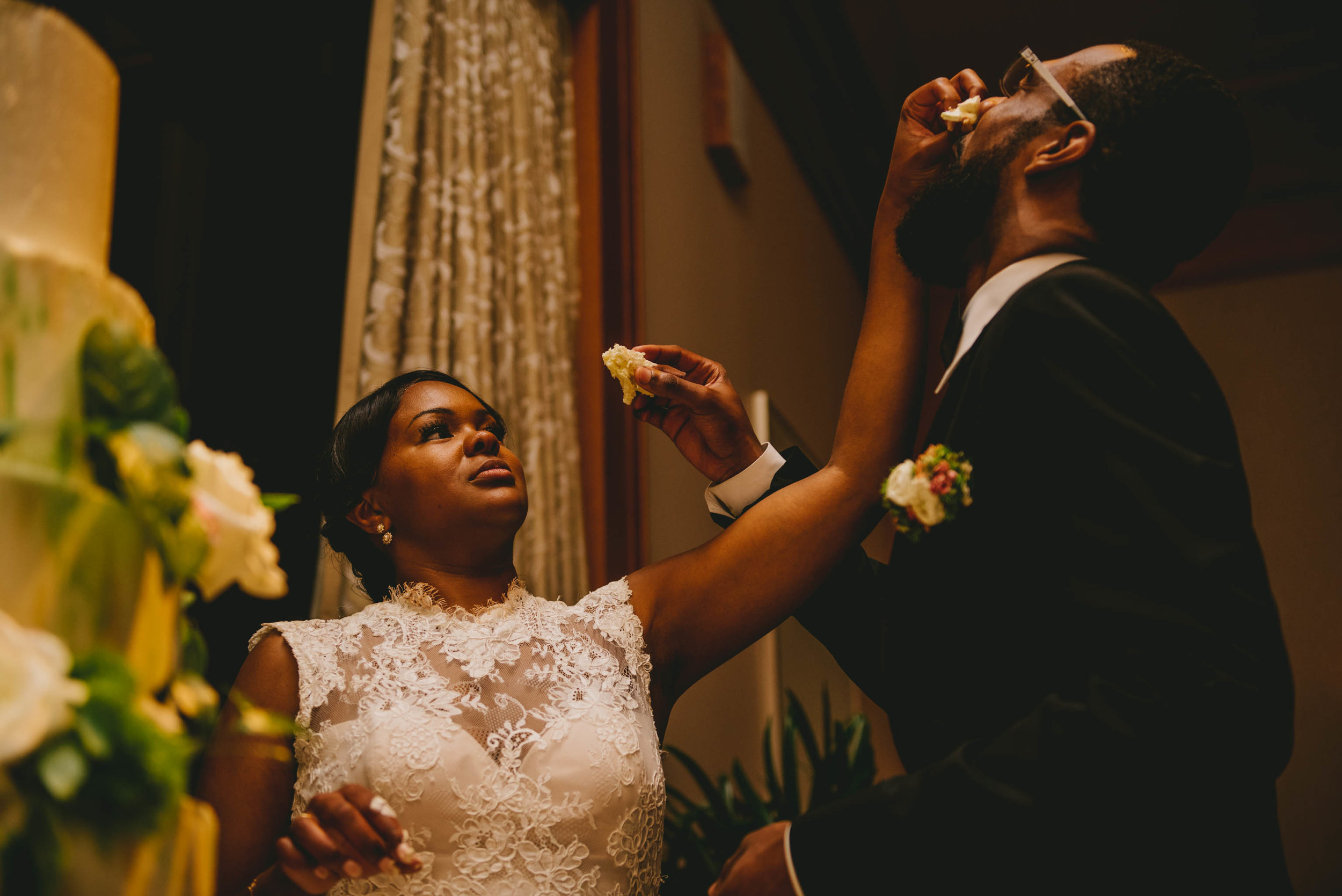 The bride smashes a piece of cake in the grooms face at the Raleigh, NC wedding