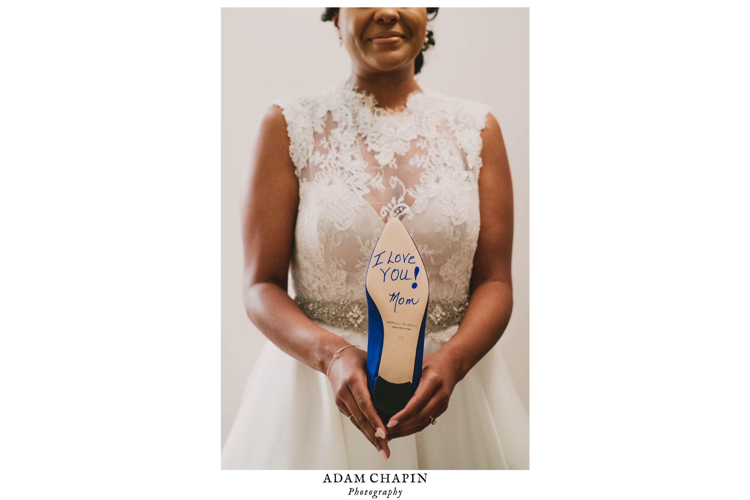 Bride holding her Manolo Blahnik heels with a note from her mom on the bottom