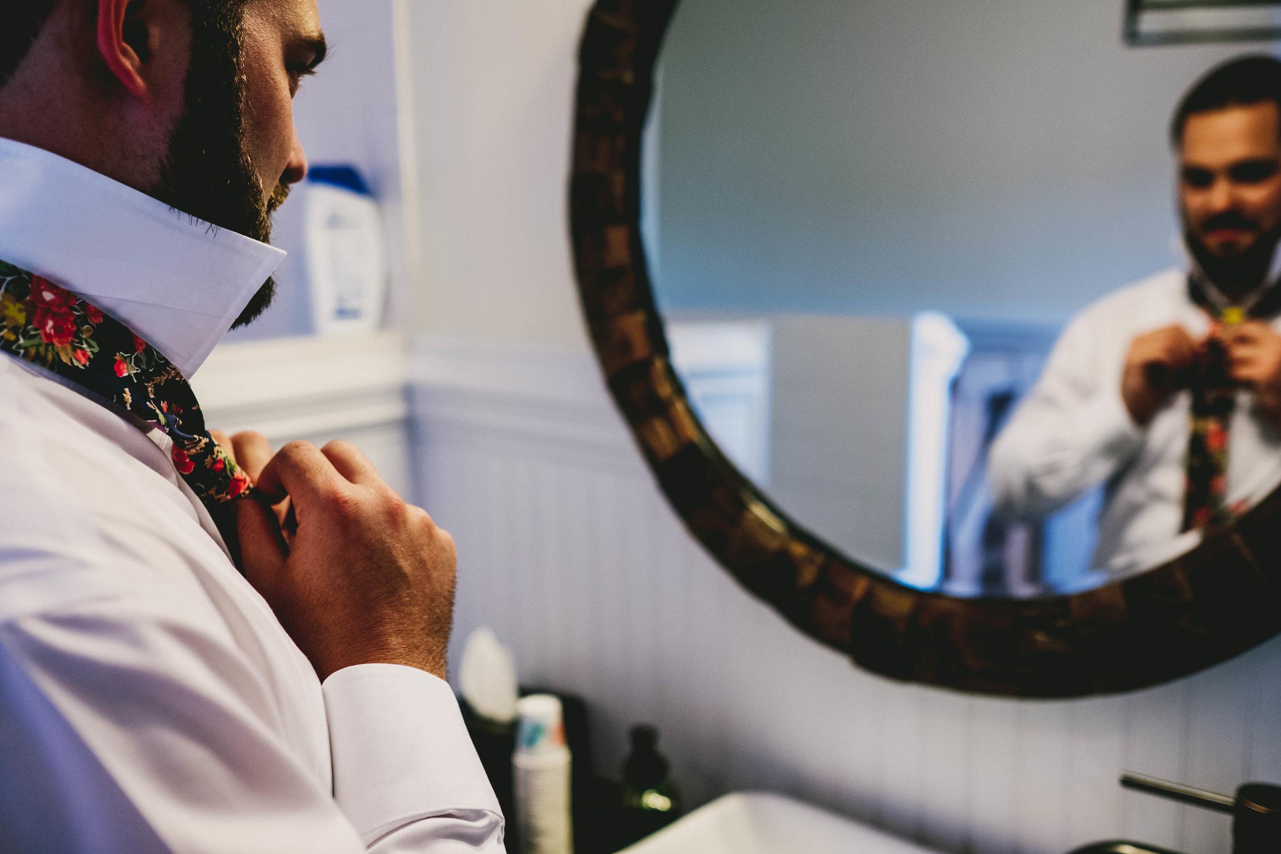 mims-house-wedding-groom-tieing-tie.jpg