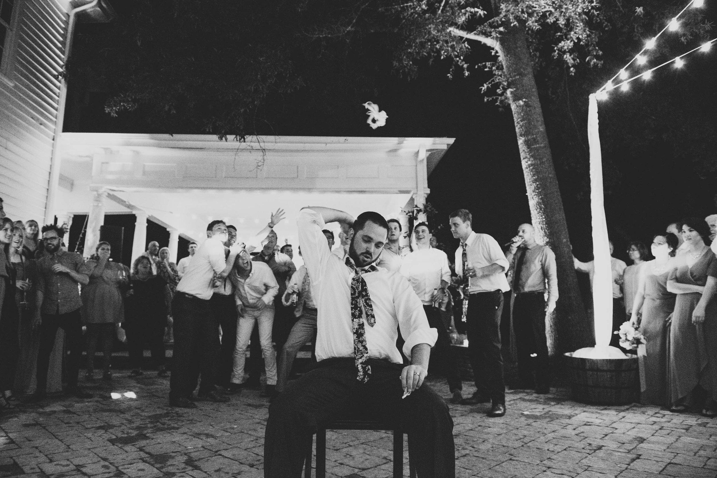 mims-house-wedding-groom-tosses-garter-photo.jpg