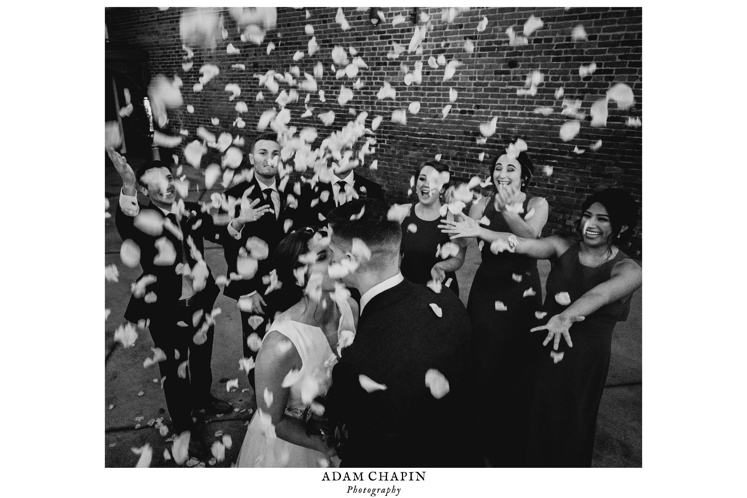 bride and groom being showered with flowers by wedding party while kissing
