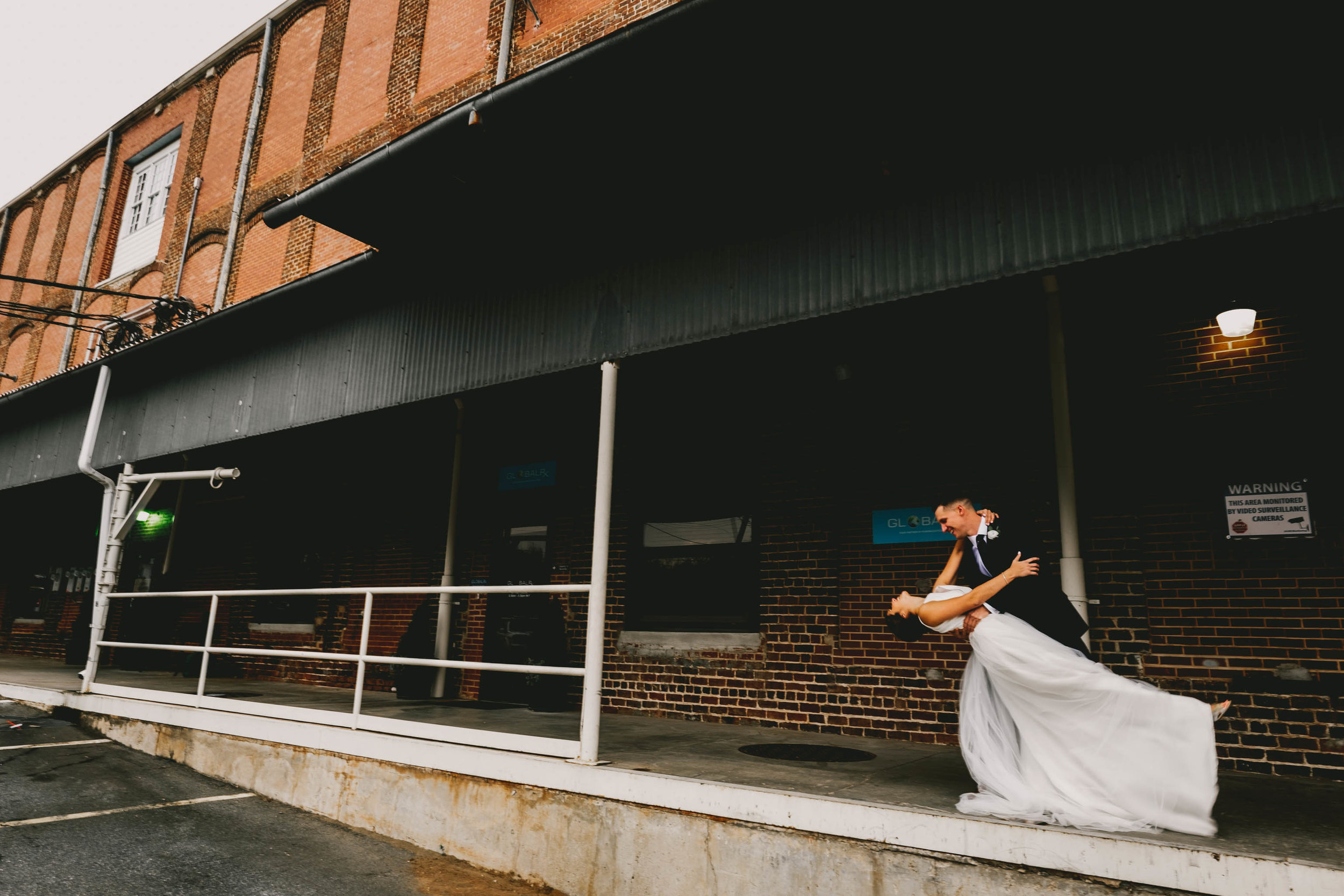 groom dips bride while dancing on loading dock