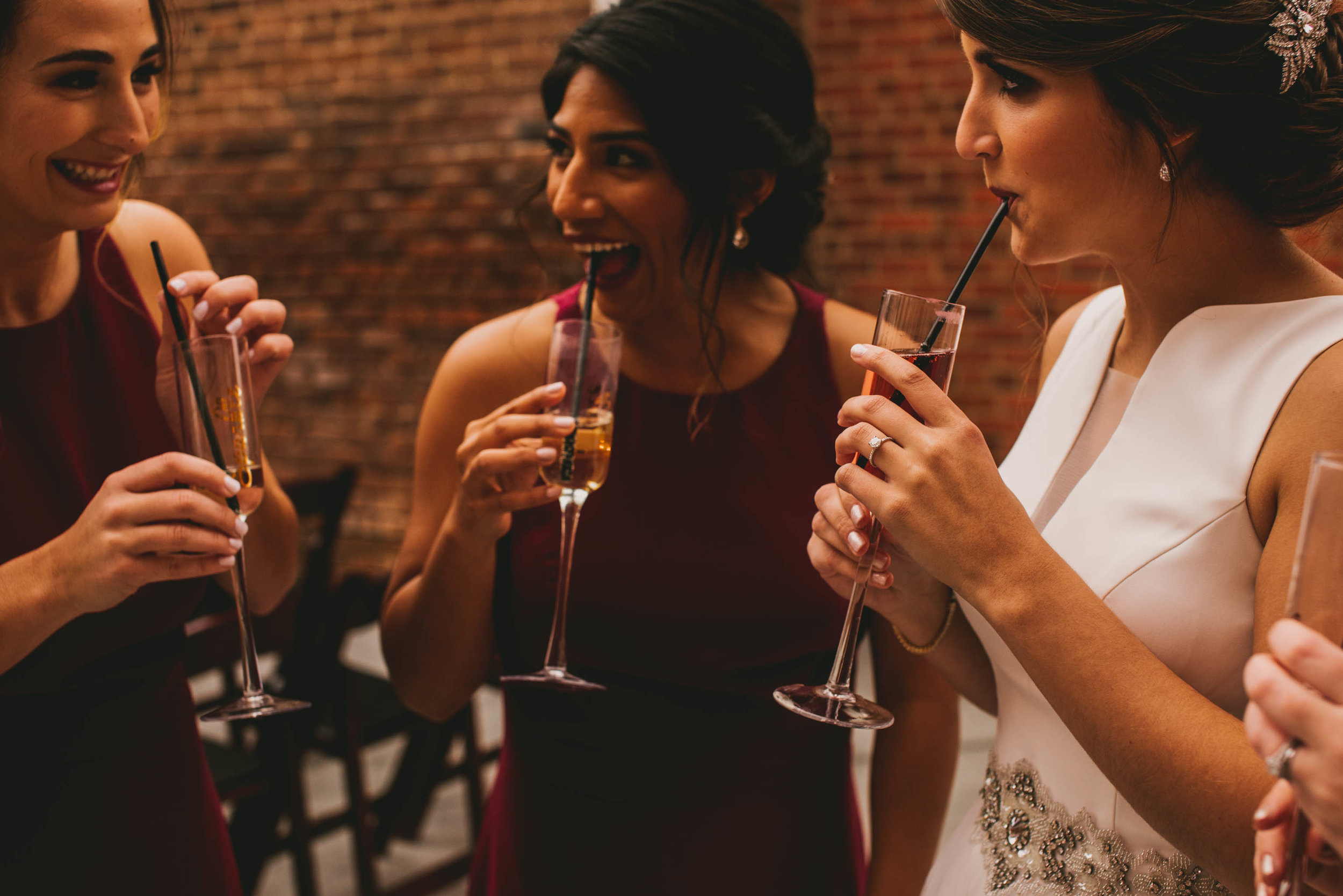 bride and bridesmaids having a drink and laughing