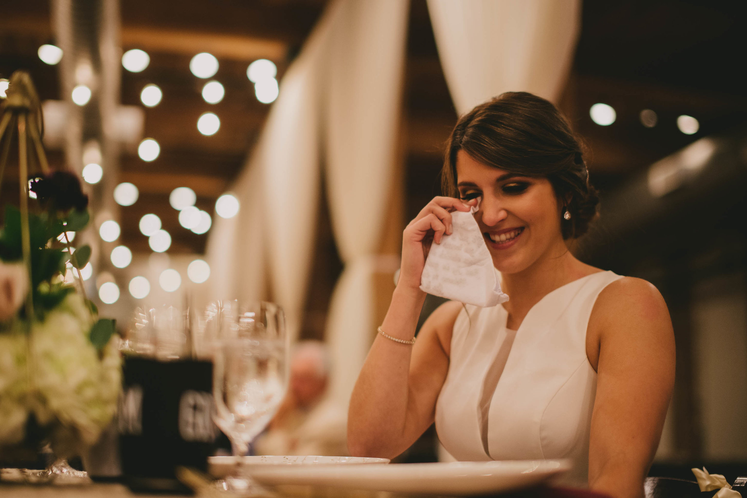 bride crying and laughing during father of the brides toast