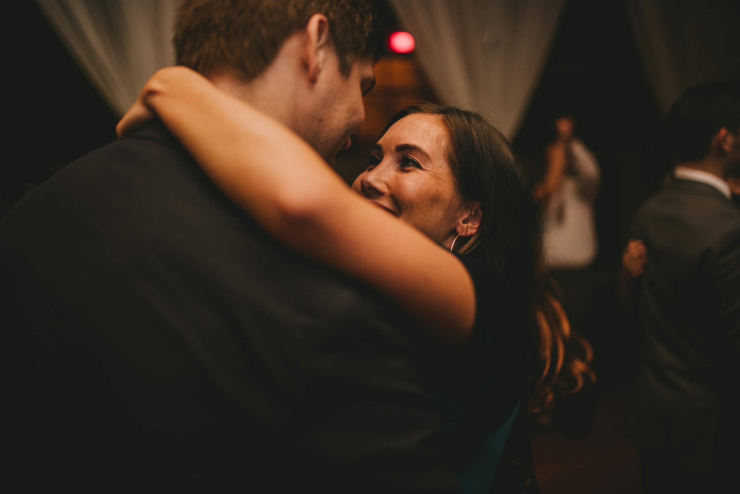 wedding guests embrace during dance