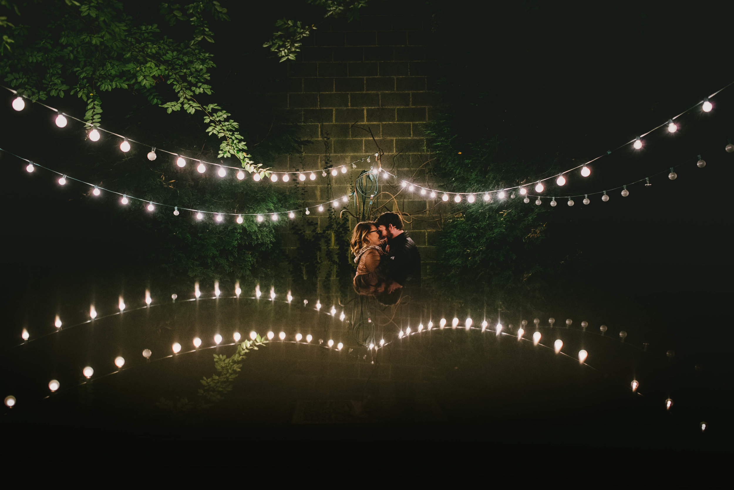 Couple getting close during their engagement photos at the Lindley Park Filling Station under a reflection of the garden tea lights