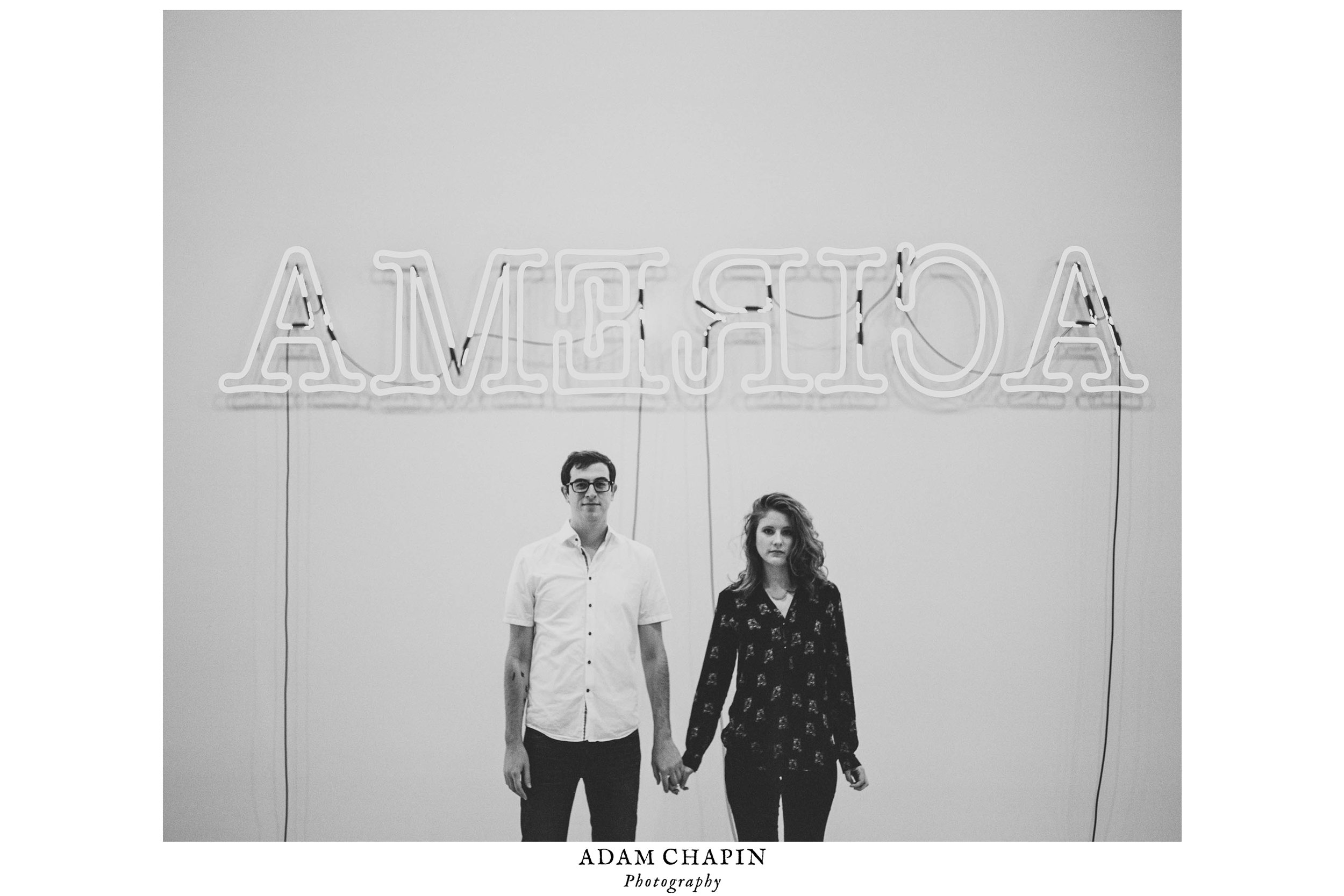 "Couple holding hands in front of Glen Ligon's ""America"" neon piece at the Whitney Museum during their New York City engagement photos"