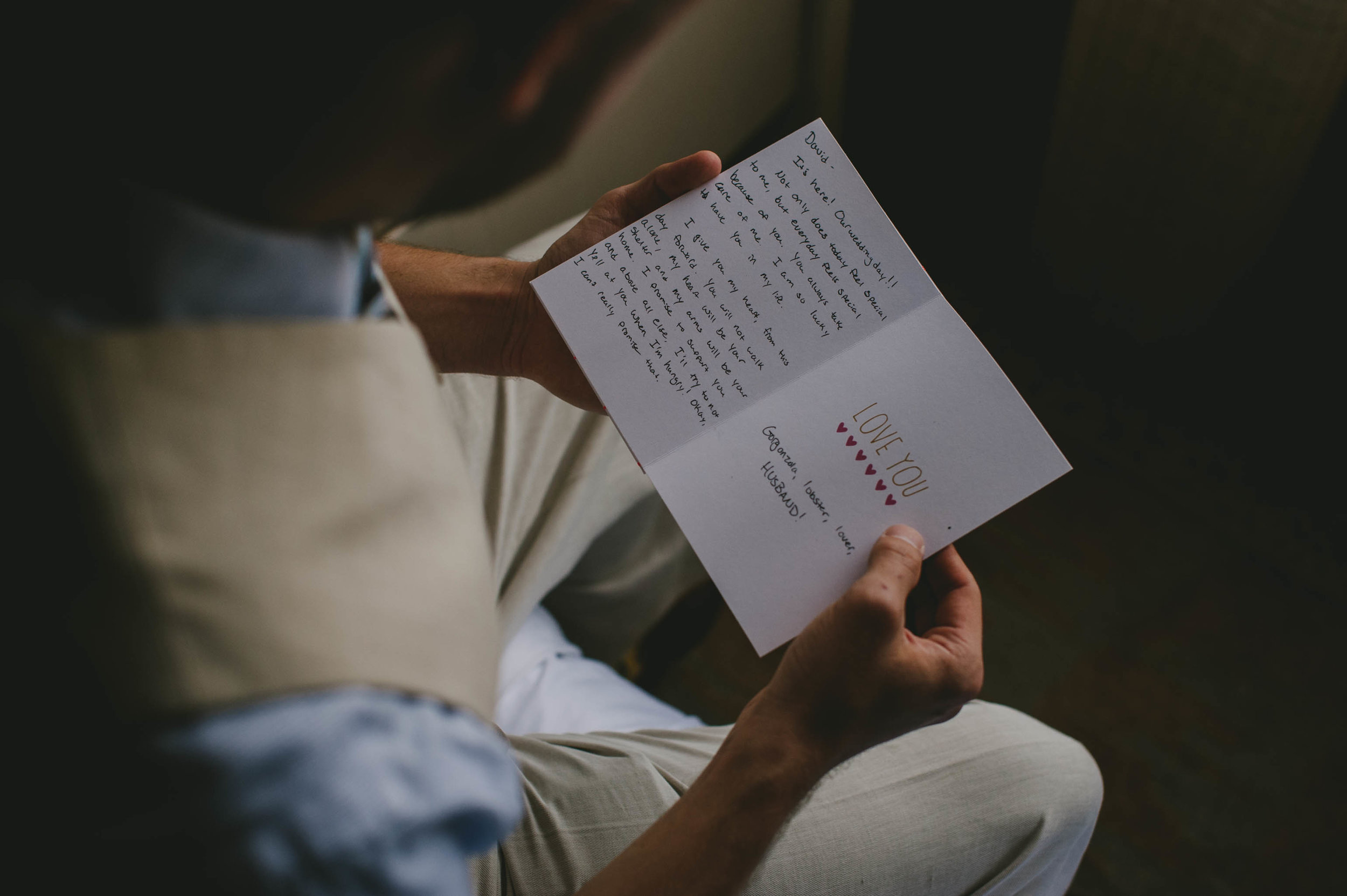 groom reading bride's card to him before their wedding ceremony
