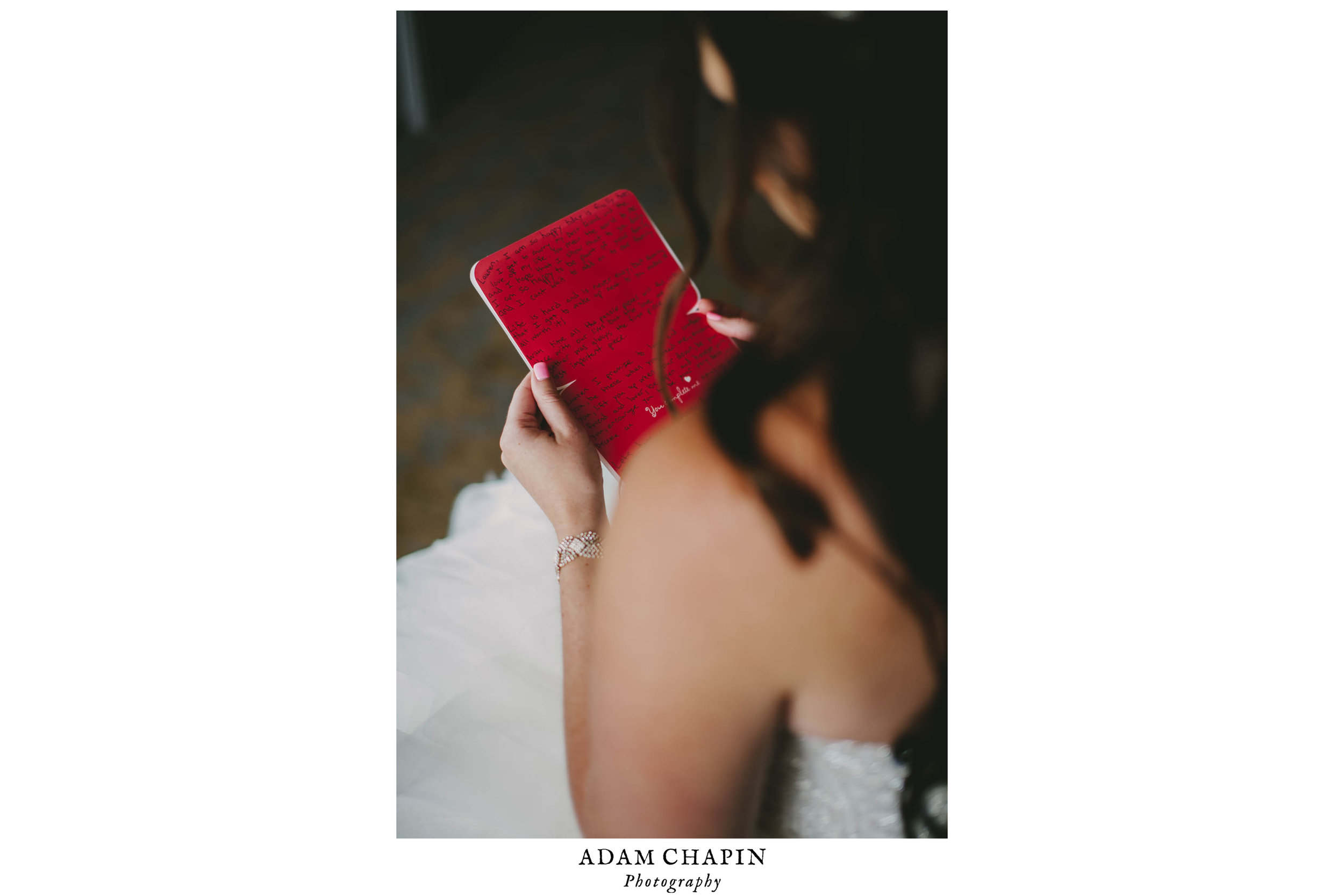 bride reading grooms card to her before their wedding ceremony