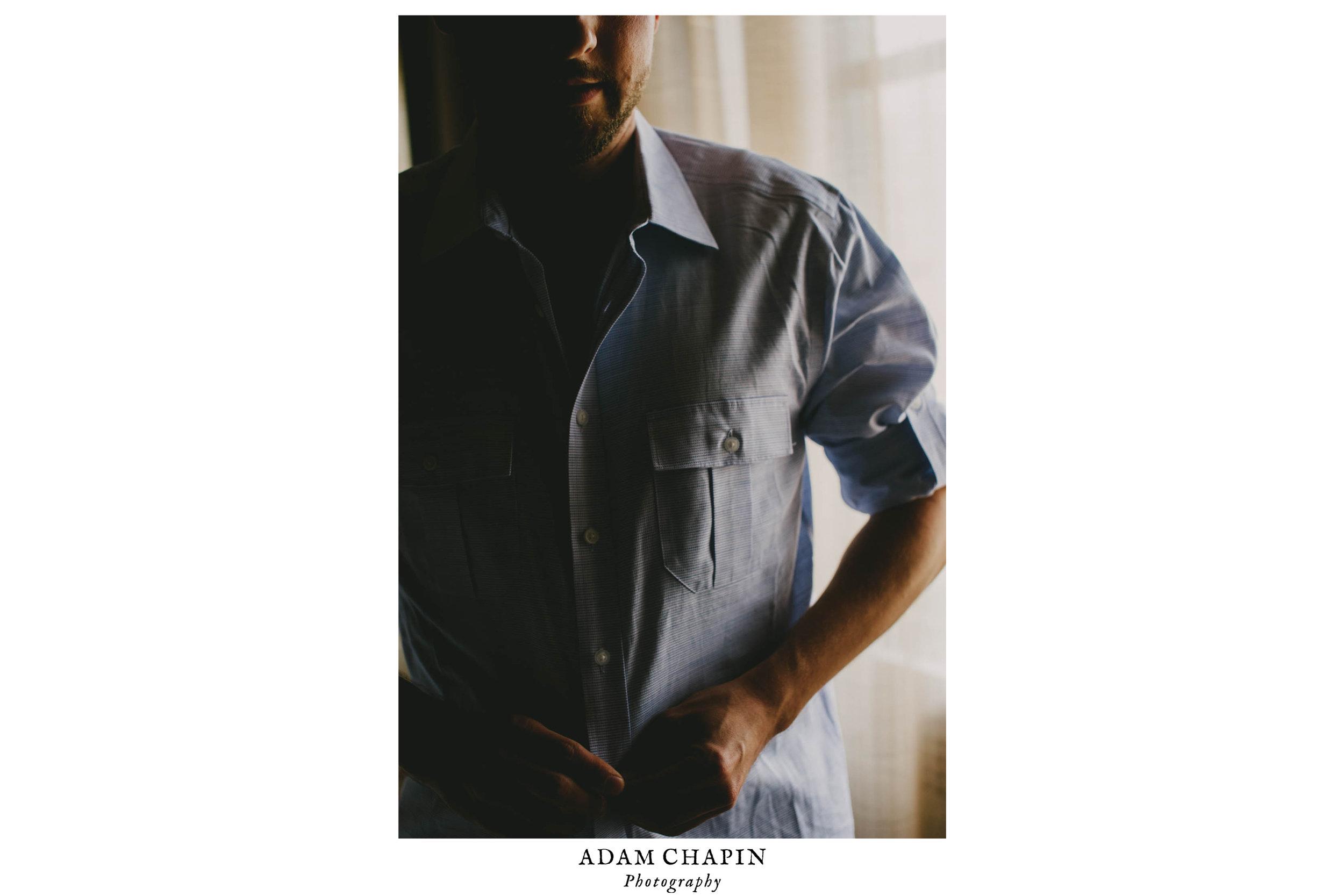 groom buttoning shirt at 21c hotel durham