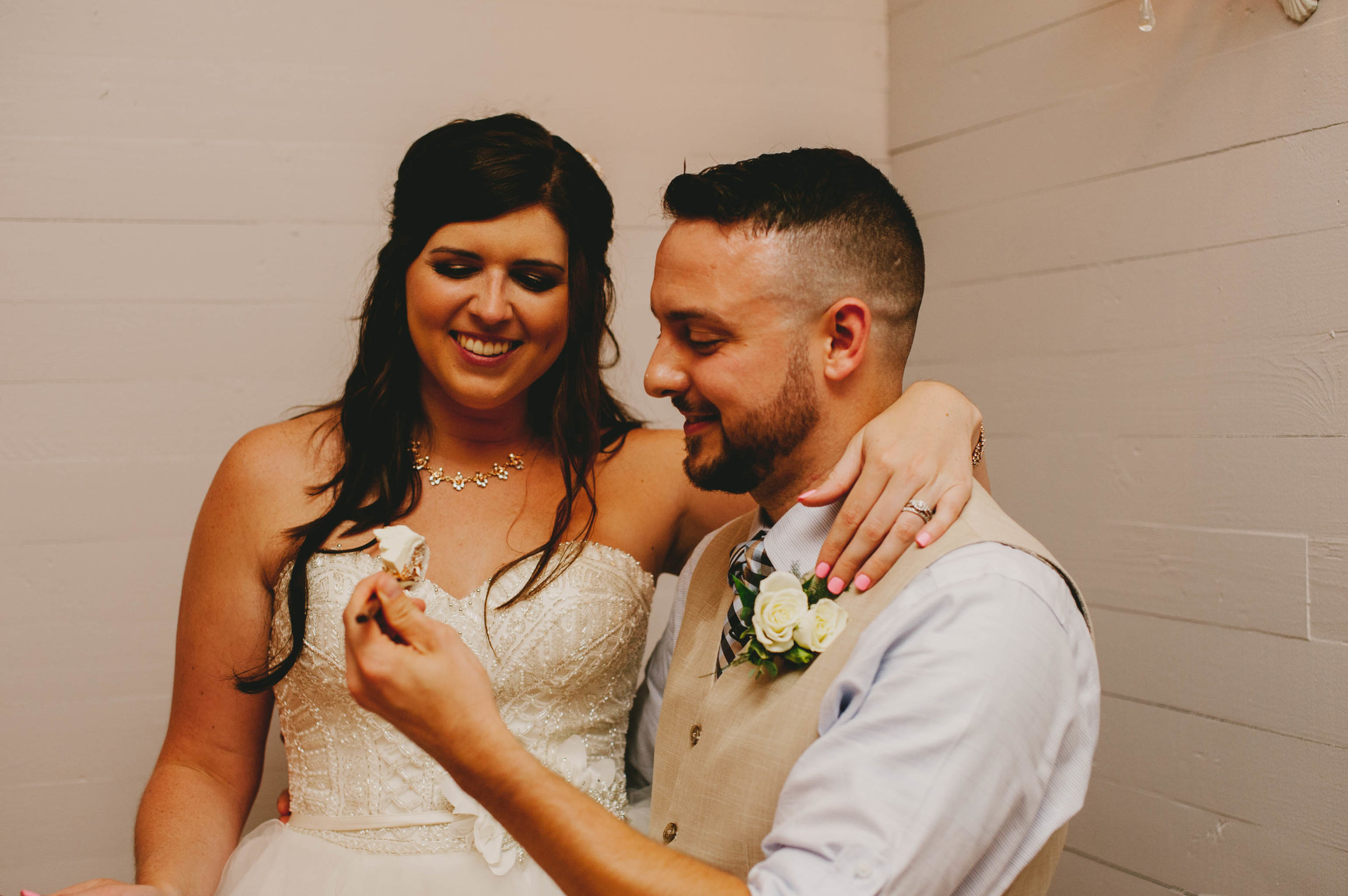 bride and groom get ready for eating their wedding cake