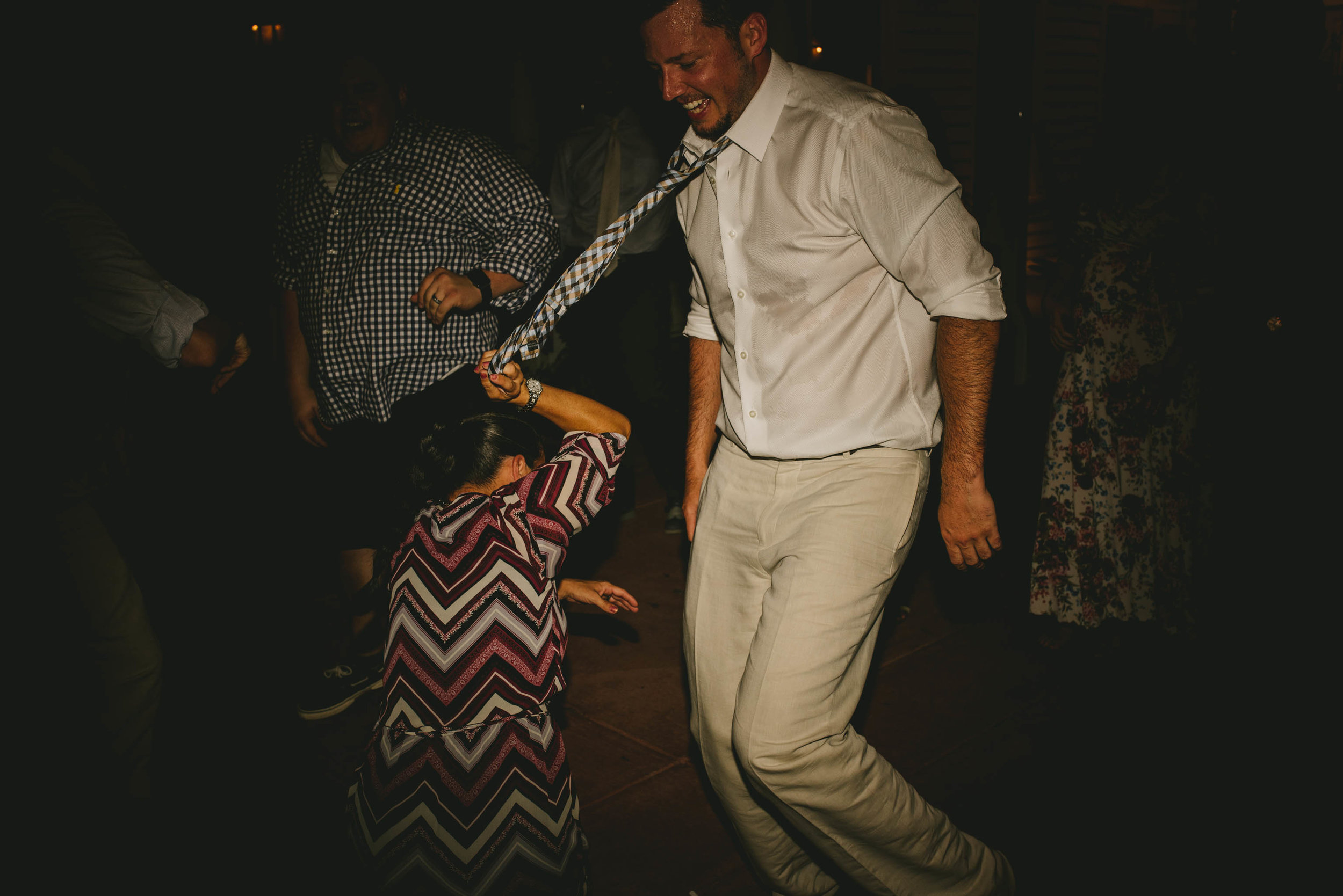 best man getting tie pulled while dancing at mims house wedding reception