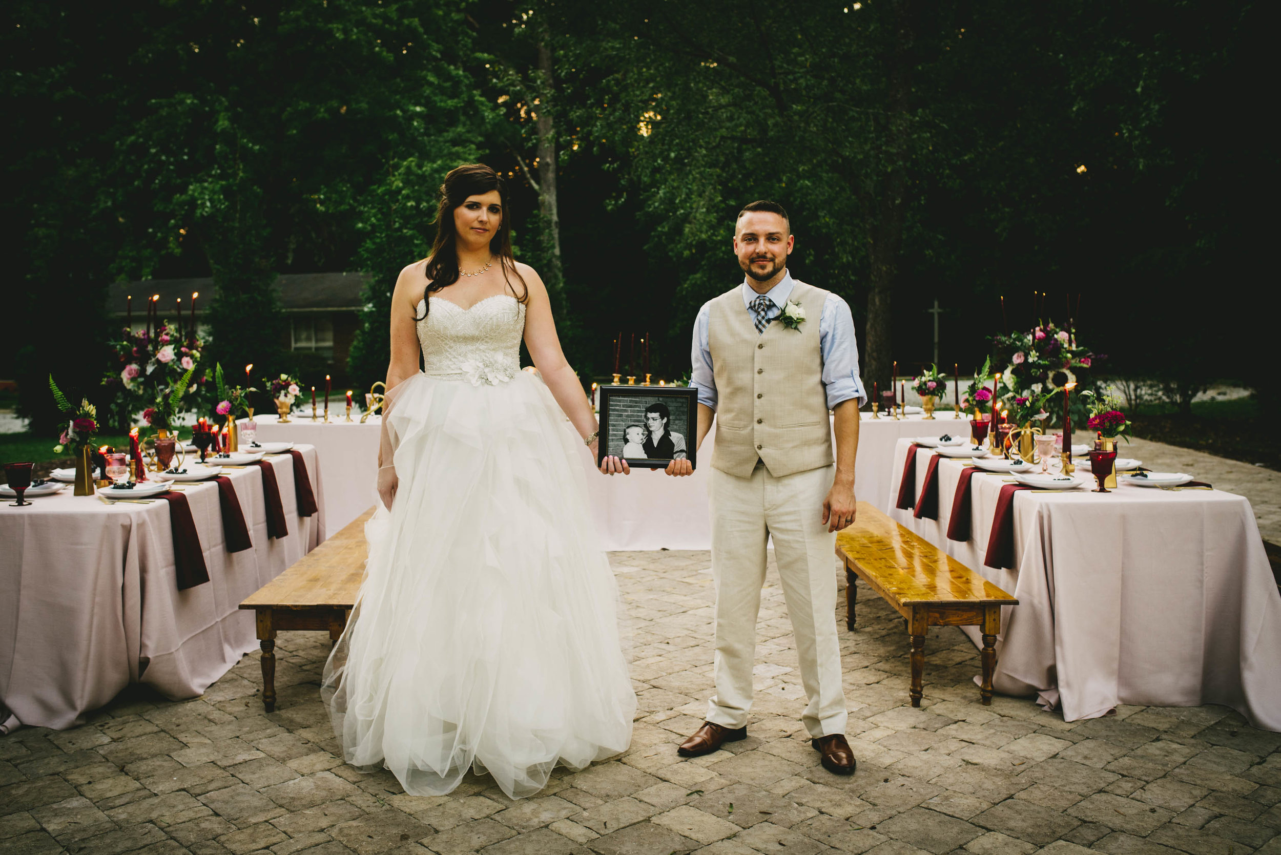 bride and groom posing with photo of grooms dad
