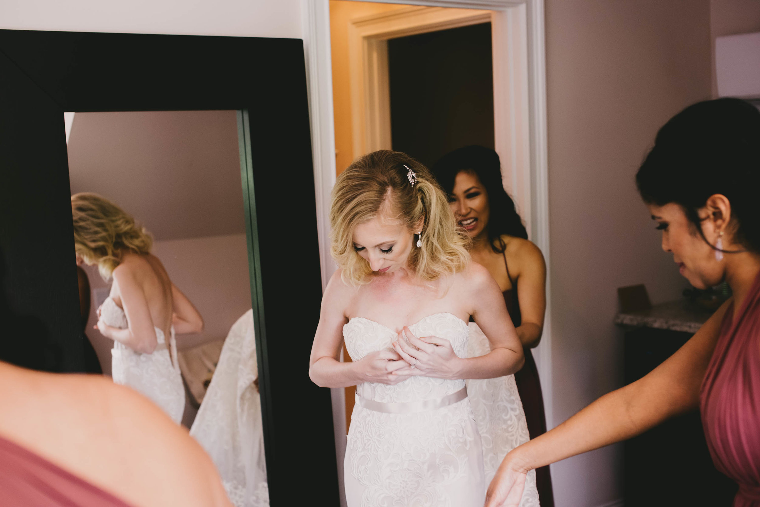 bride getting on her dress with help of her bridesmaids