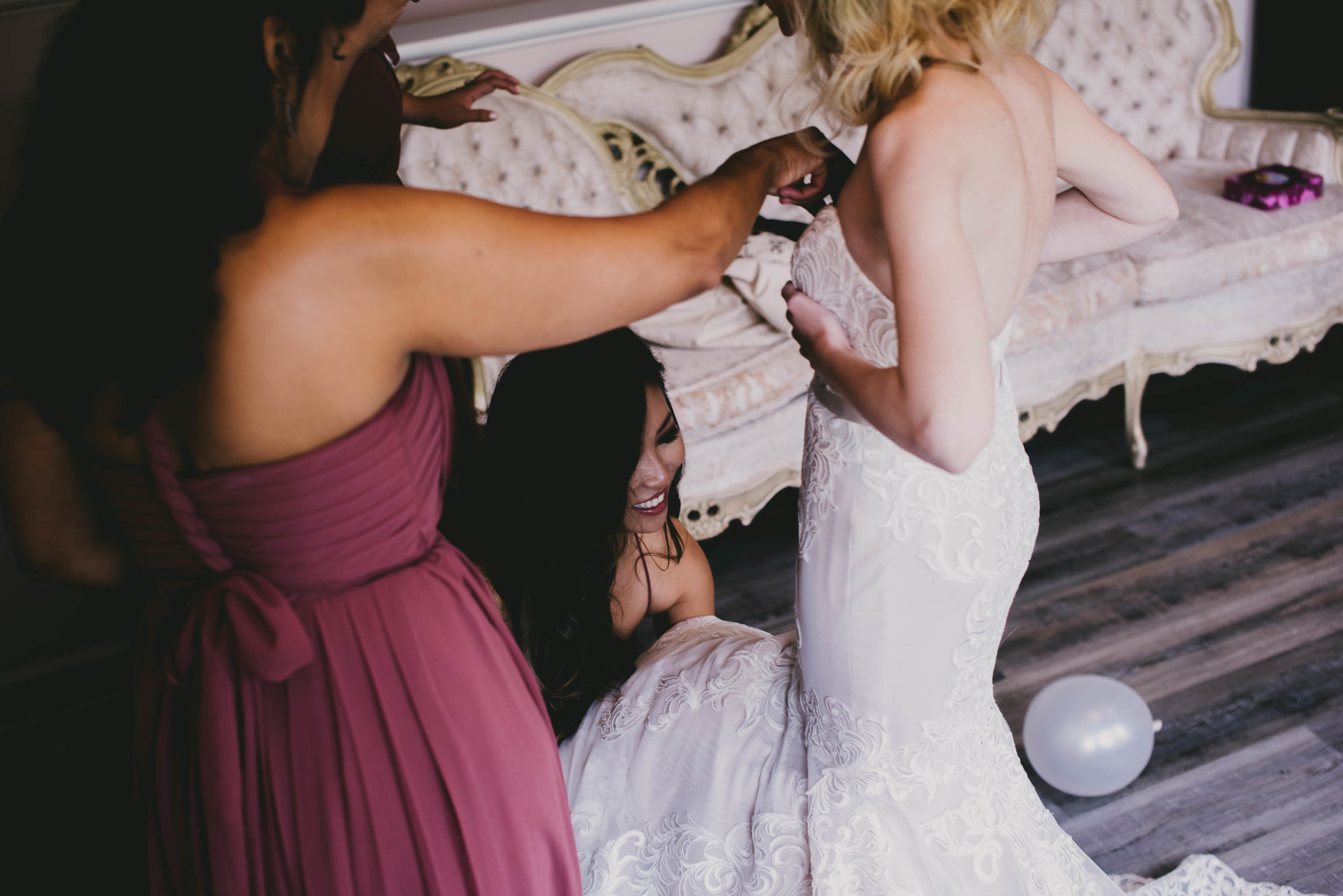 maid of honor helping to fix the brides dress