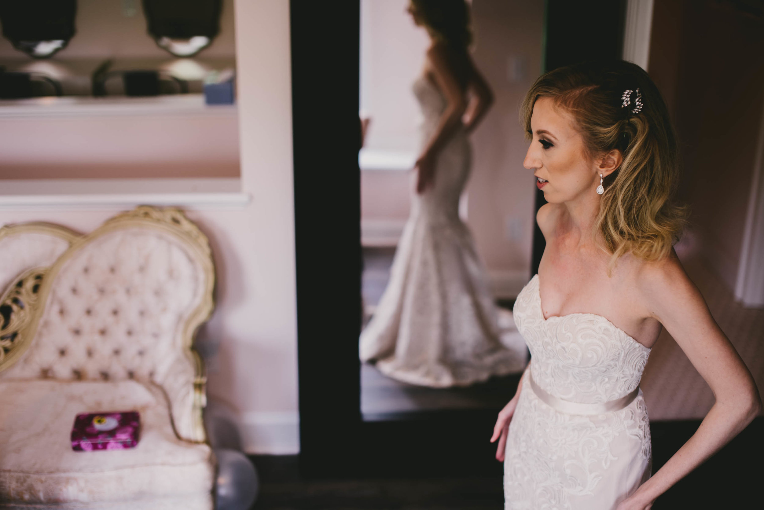 bride and her reflection in the mirror as she is doing final touches before the wedding