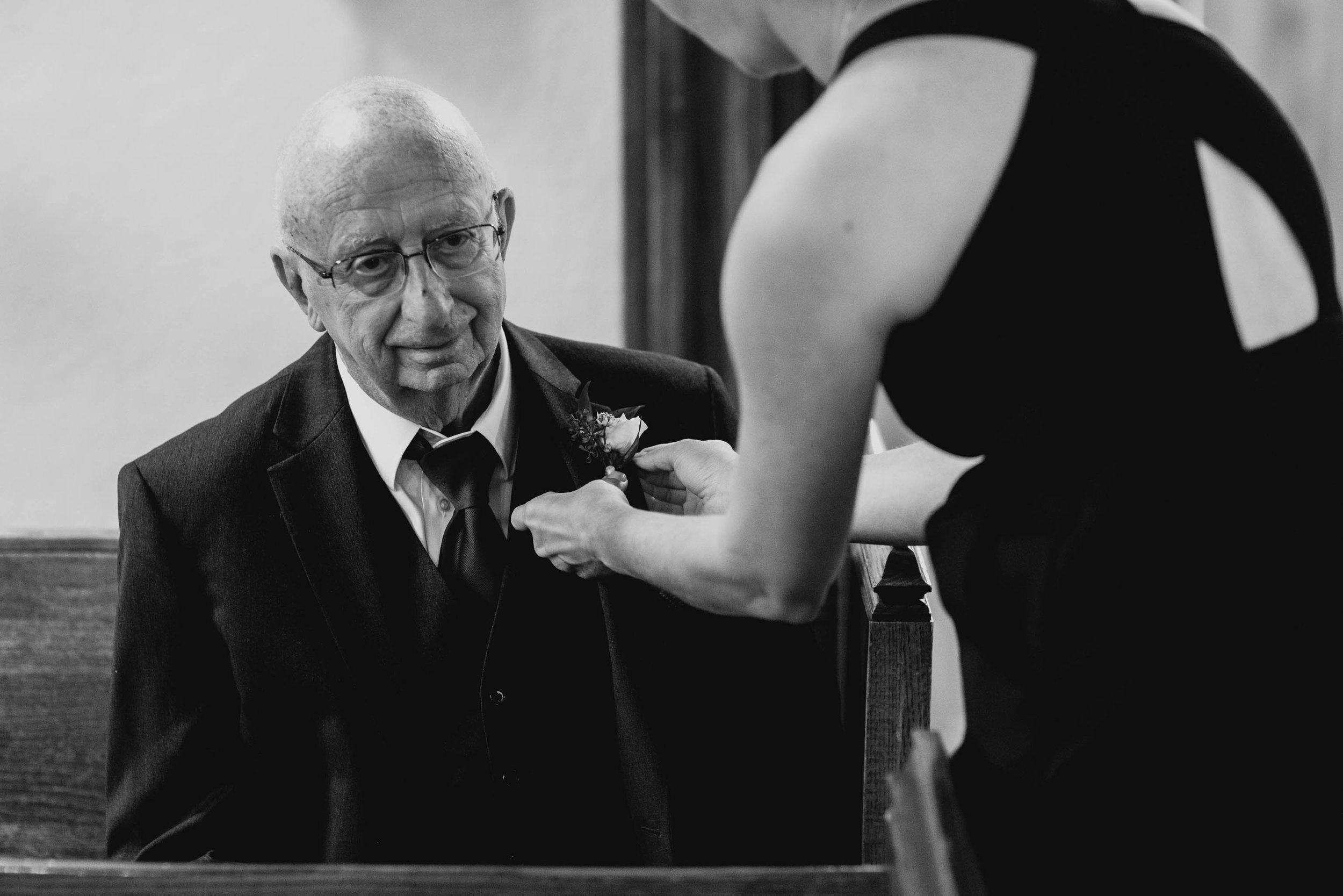 father of the bride having boutonniere pinned on his lapel