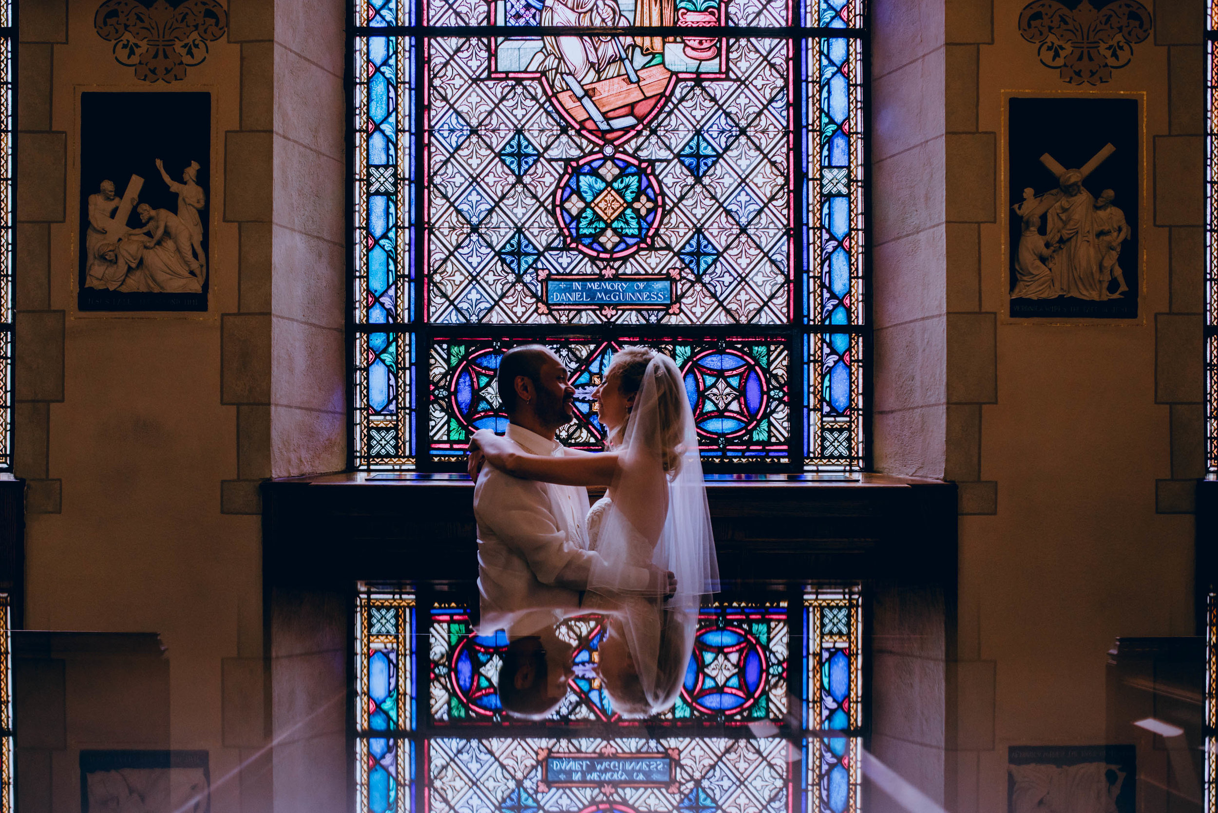 bride and groom reflected in stain glass window of Sacred Heart Cathedral