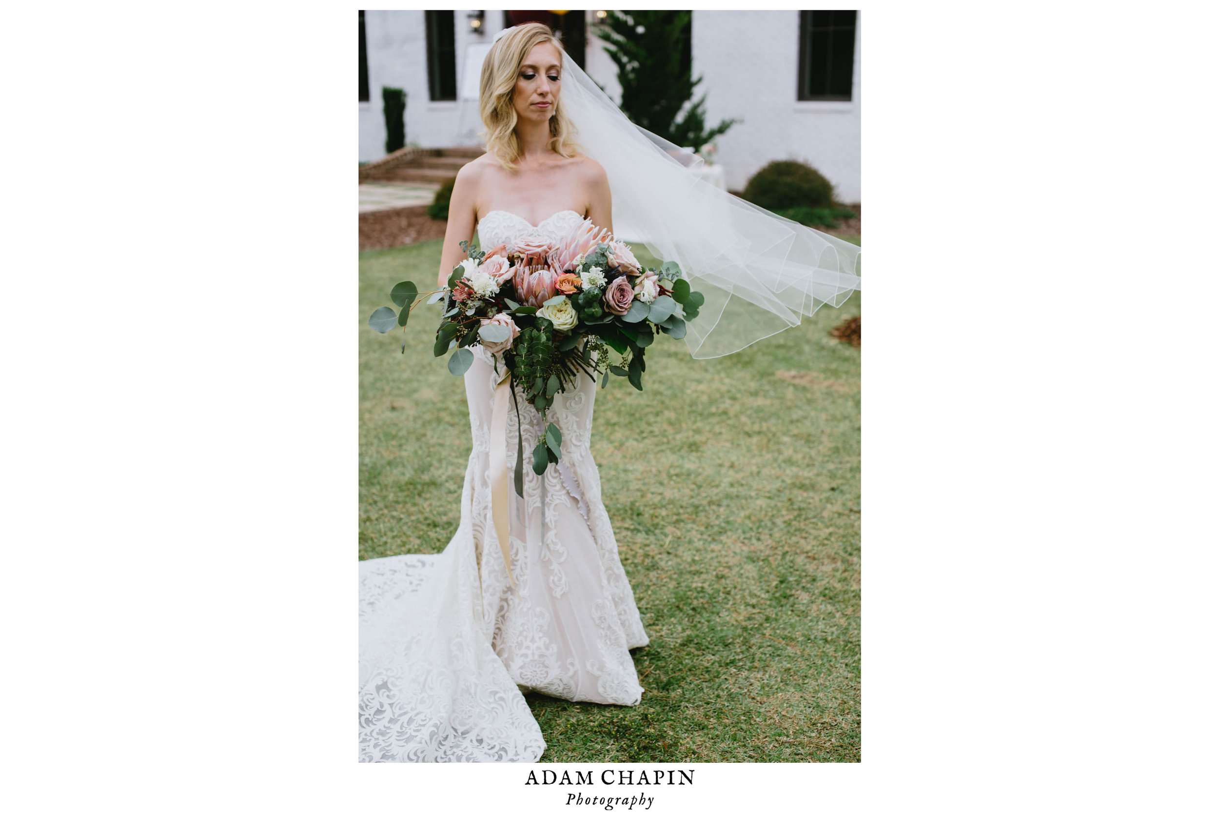portrait of the bride holding her bouquet as the wind plays with her veil