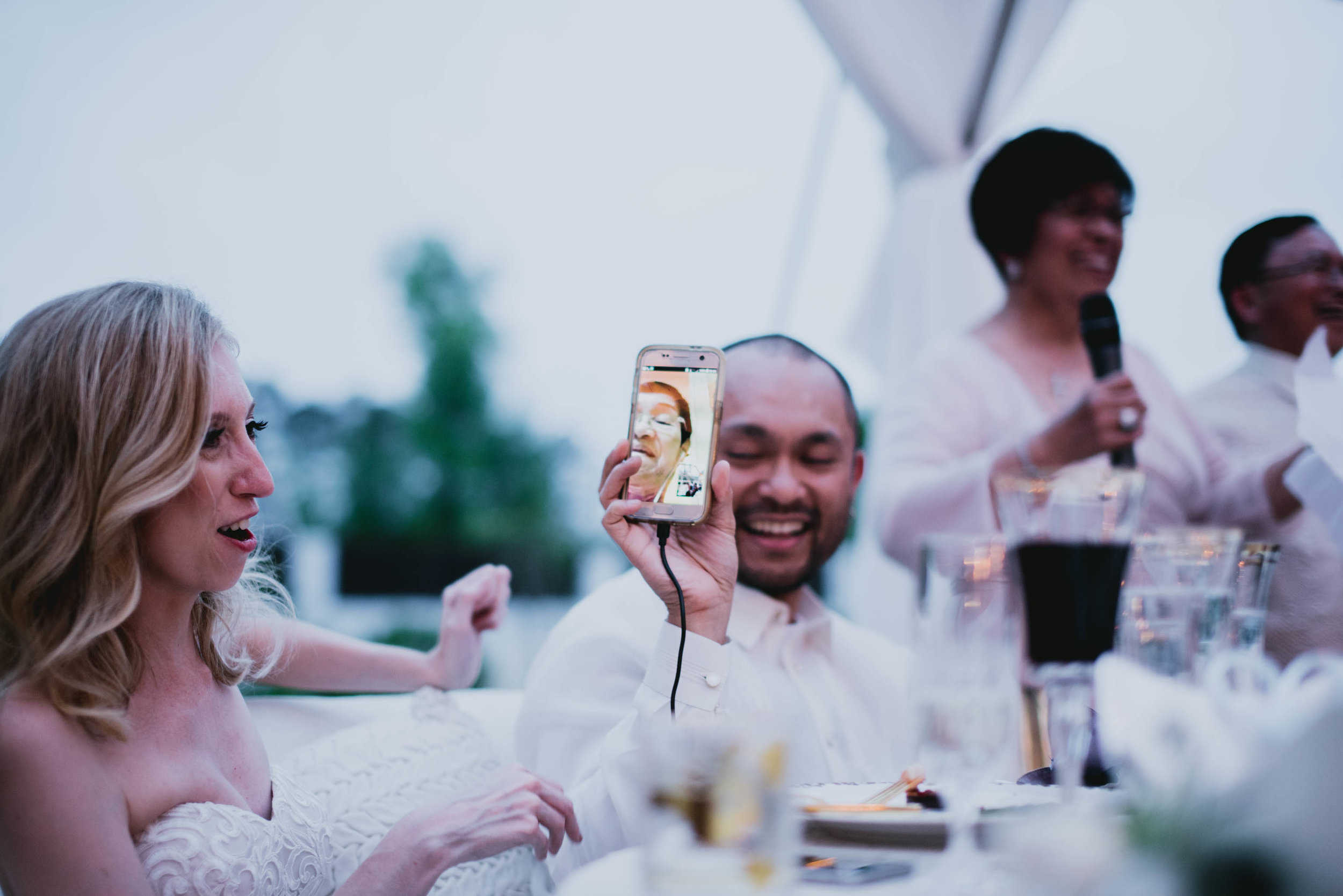 groom holding up phone with his grandmother on it via facetime