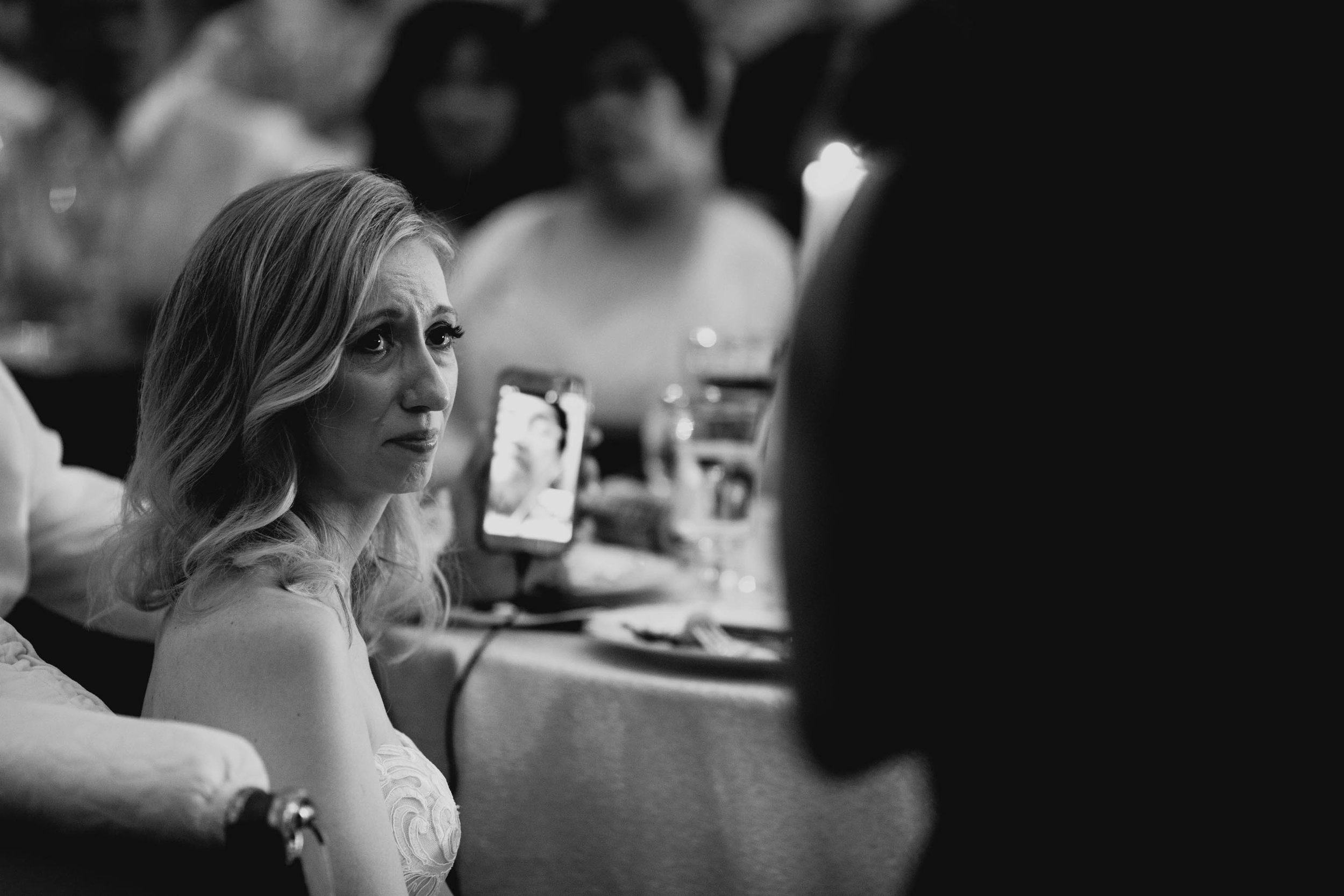 bride tearing up during maid of honor's speech