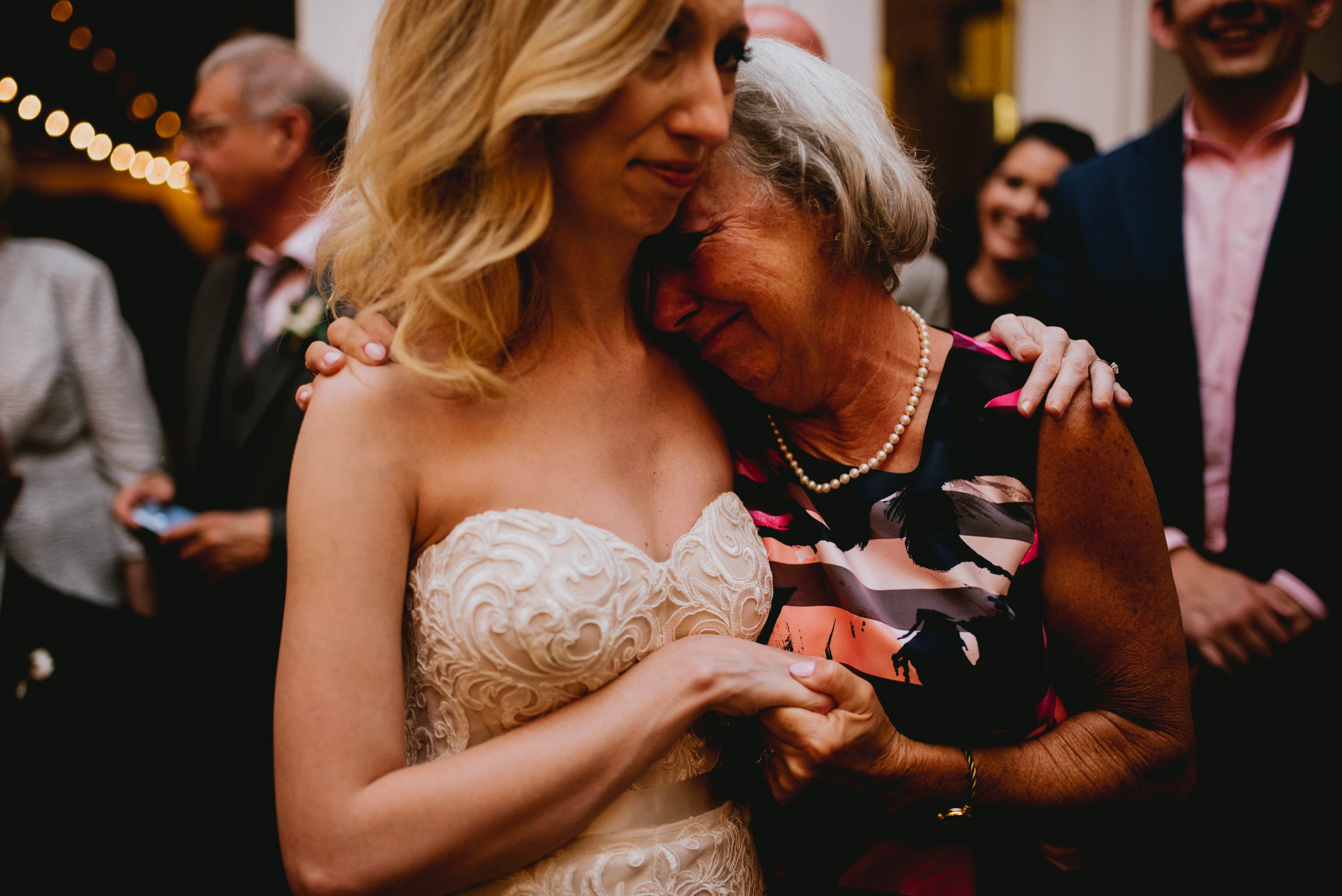 bride and guest sharing an emotional hug during reception