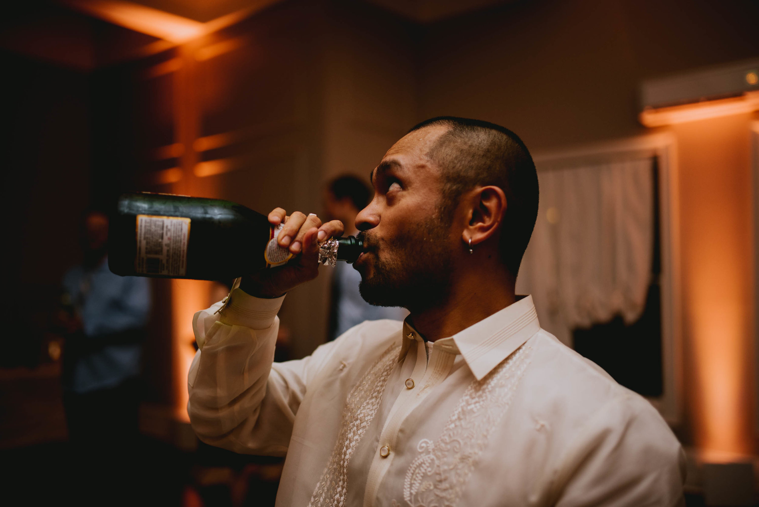 groom throwing back some champagne during wedding reception