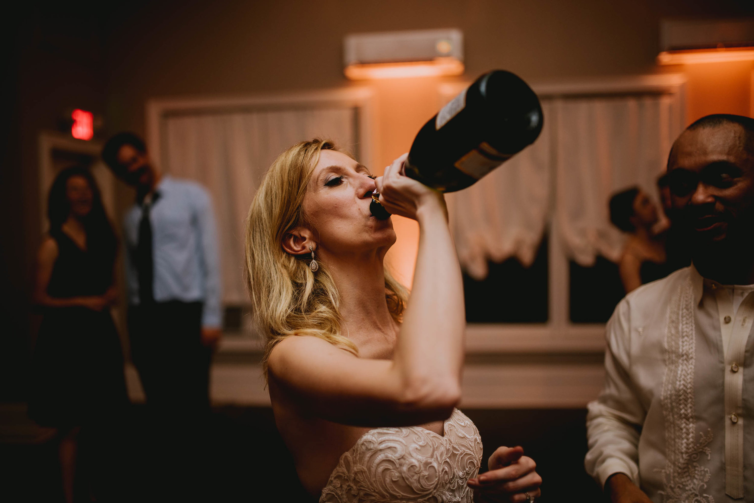 bride throwing back some champagne during wedding reception