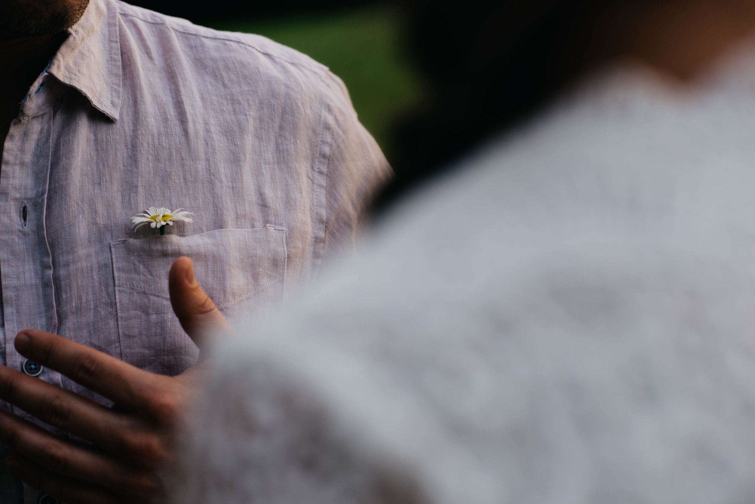detail photo of a flower sitting in a mans shirt pocket after his fiance gave it to him