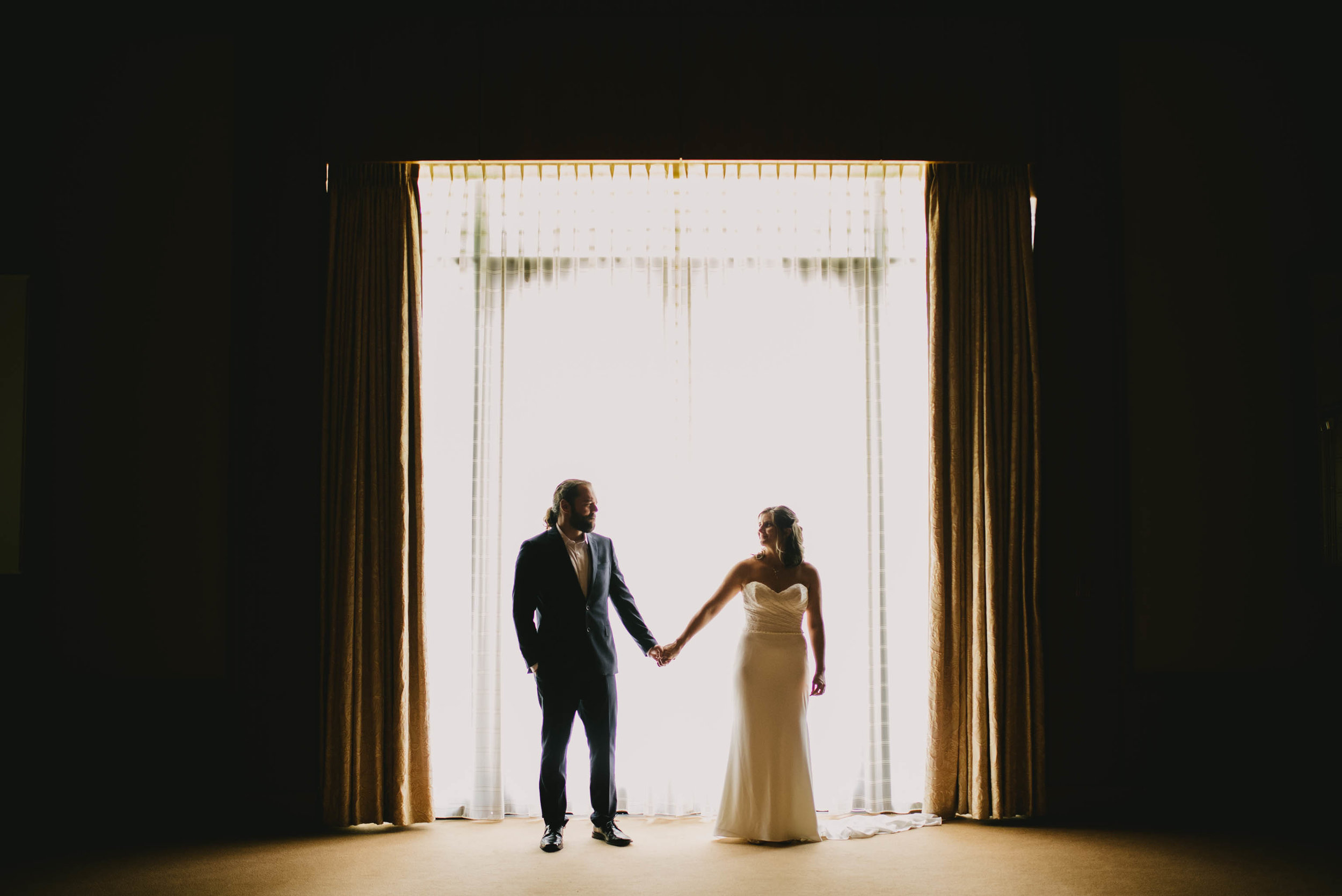 bride and groom holding hands in front of large window at Umstead Hotel and Spa