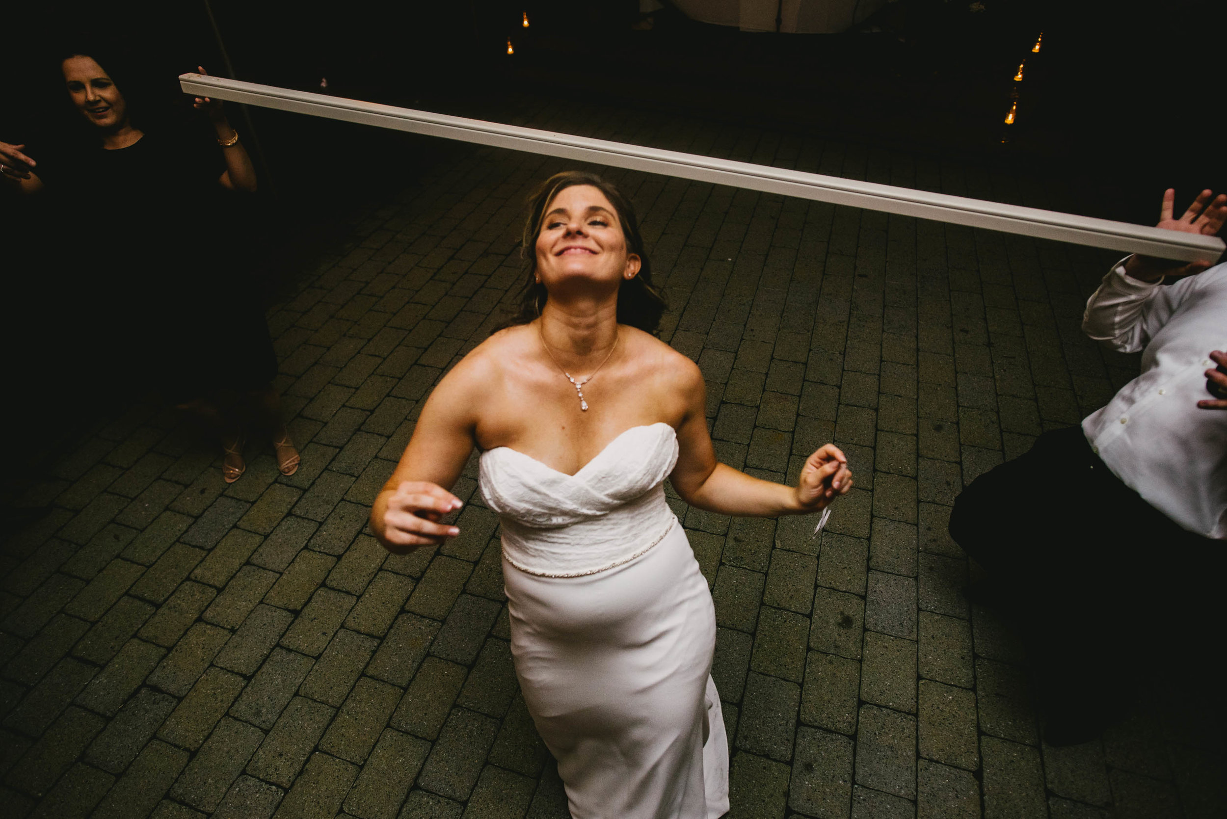 bride ducking during the limbo at her Jiddi Space and Courtyard Wedding at Sitti Restaurant