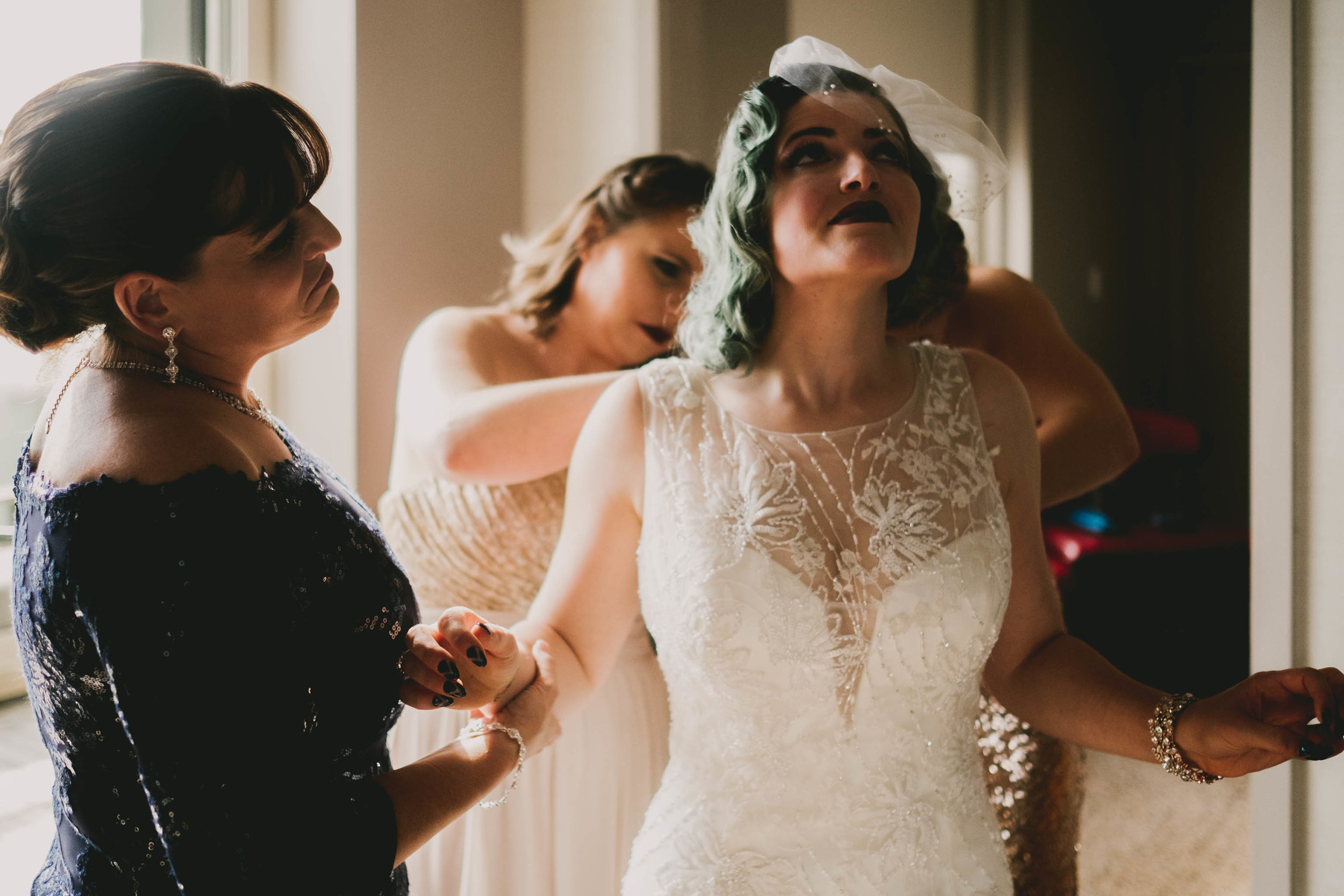 bride holding back tears while having her dress buttoned