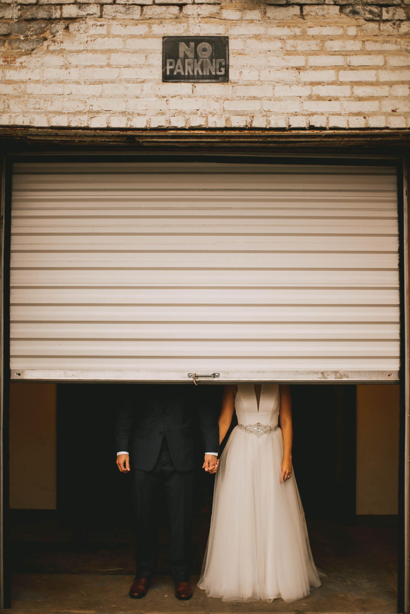 couple hiding behind a garage door at clothmill on the eno during their wedding
