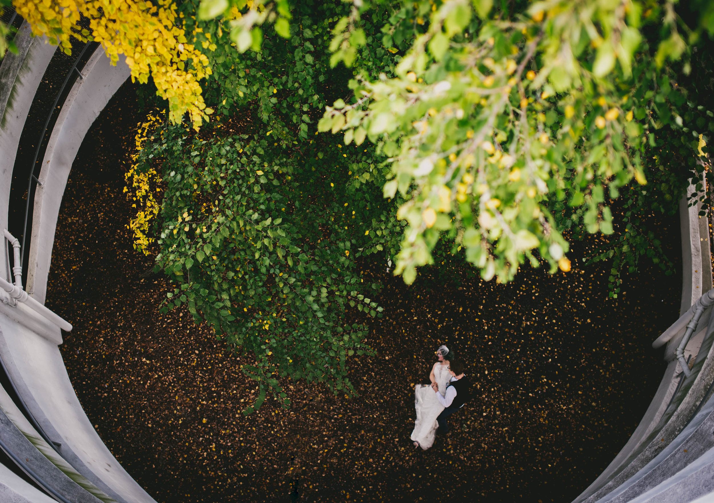 bride and groom dancing in the leaves of a parking garage in durham during their wedding