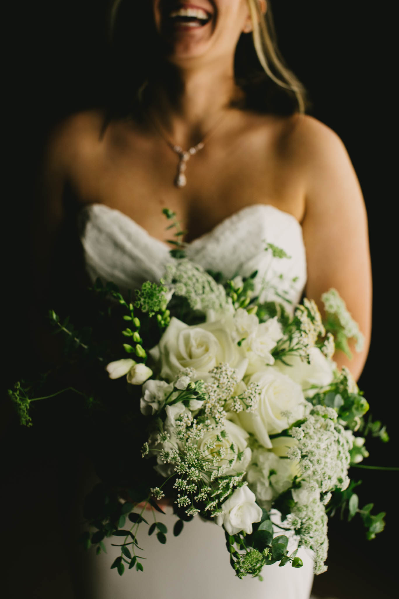 bride laughing while holding her floral bouquet at the Umstead Hotel and Spa
