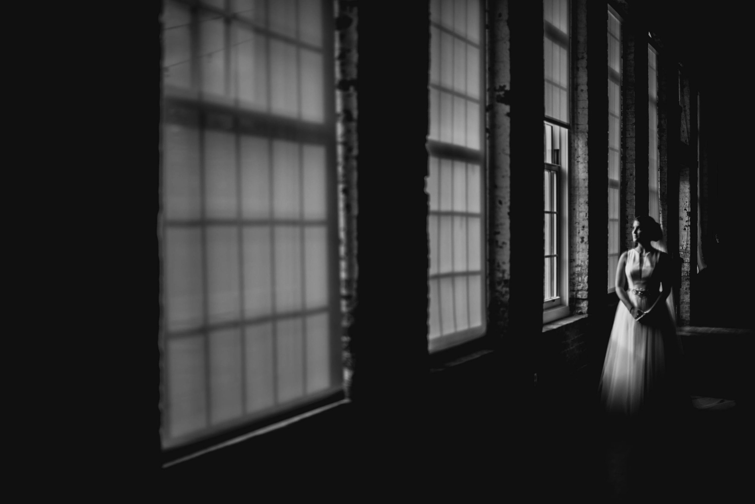 bride stnading in the window light of the clothmill on the eno