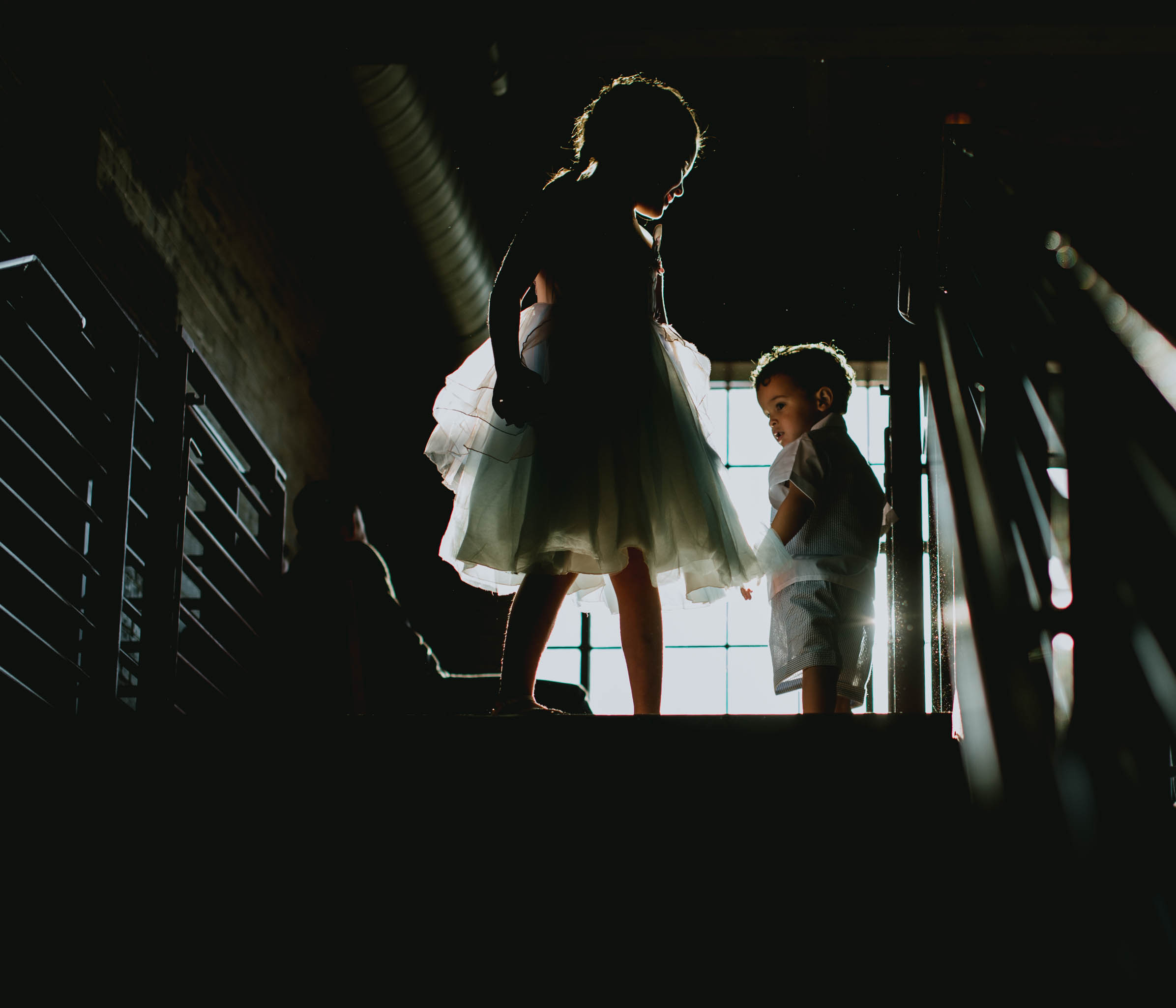 flower girl helping the ring bearer down the stairs at Haw River Ballroom wedding