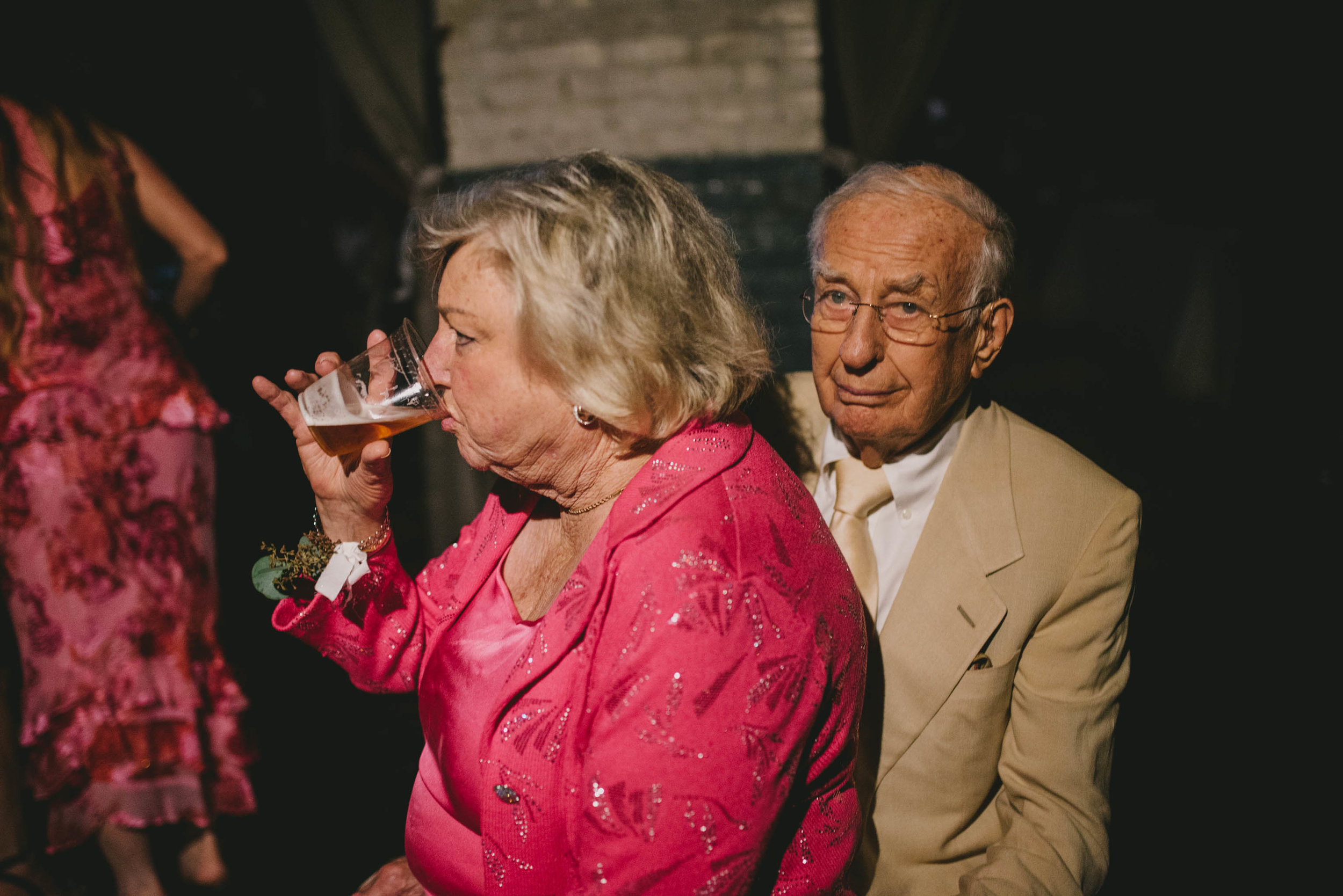 grandmother of the bride sitting on her husbands lap and drinking a beer during this forest hall at chatham mills wedding