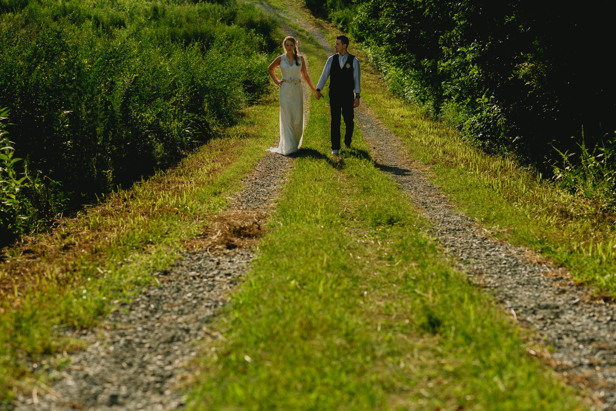 bride and groom walking down a path at their duke forest wedding
