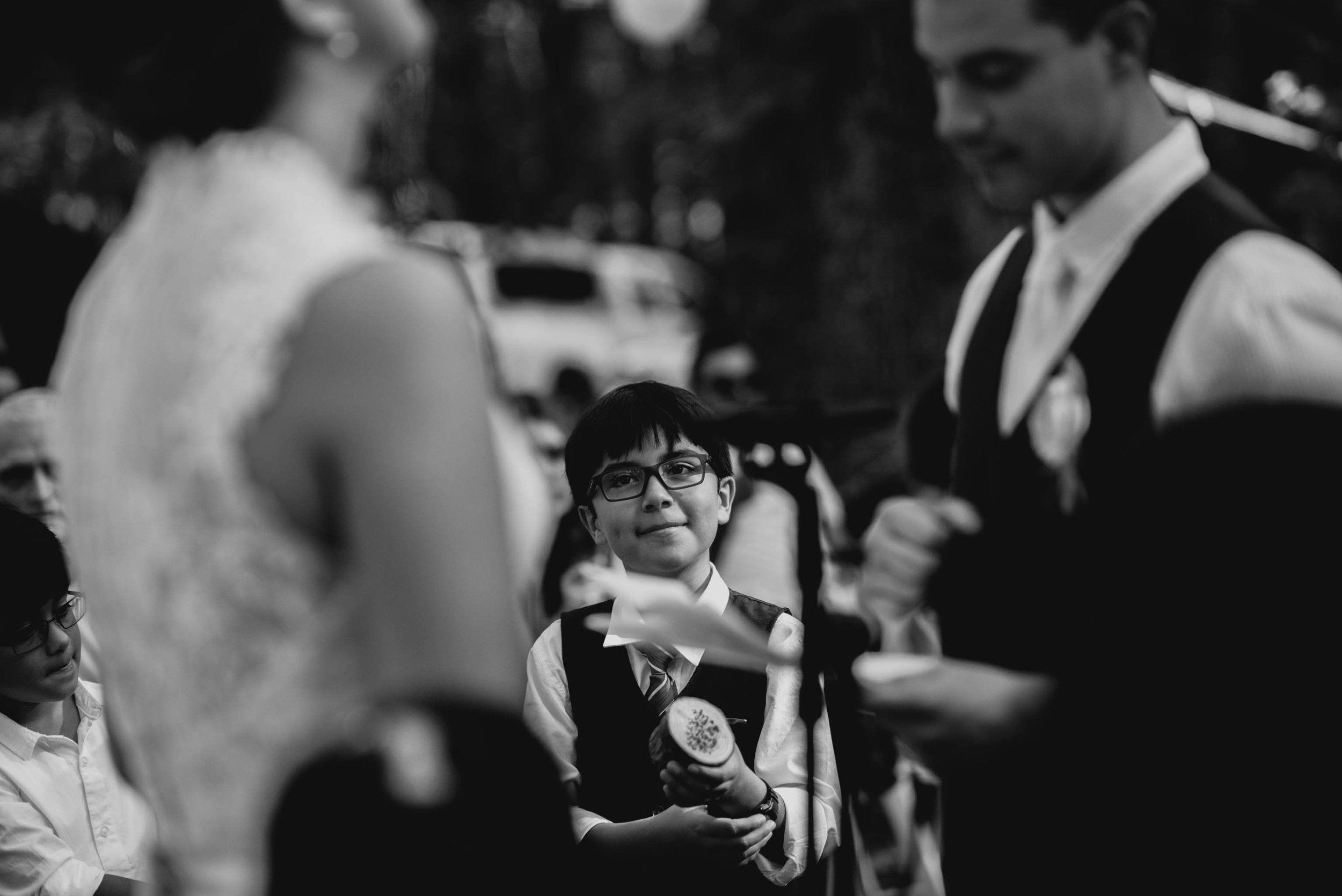 groom's nephew looking on and smiling during wedding ceremony