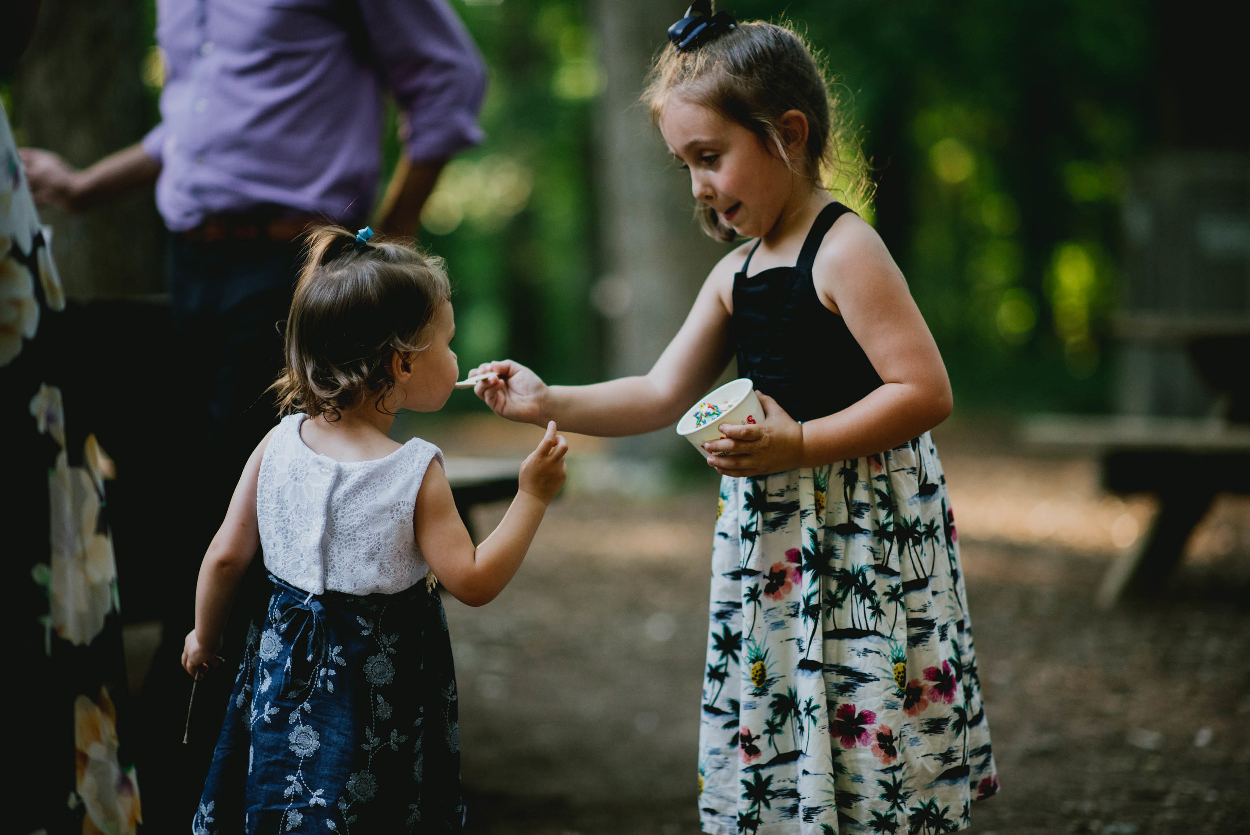 sister feeding younger sister ice cream during wedding reception