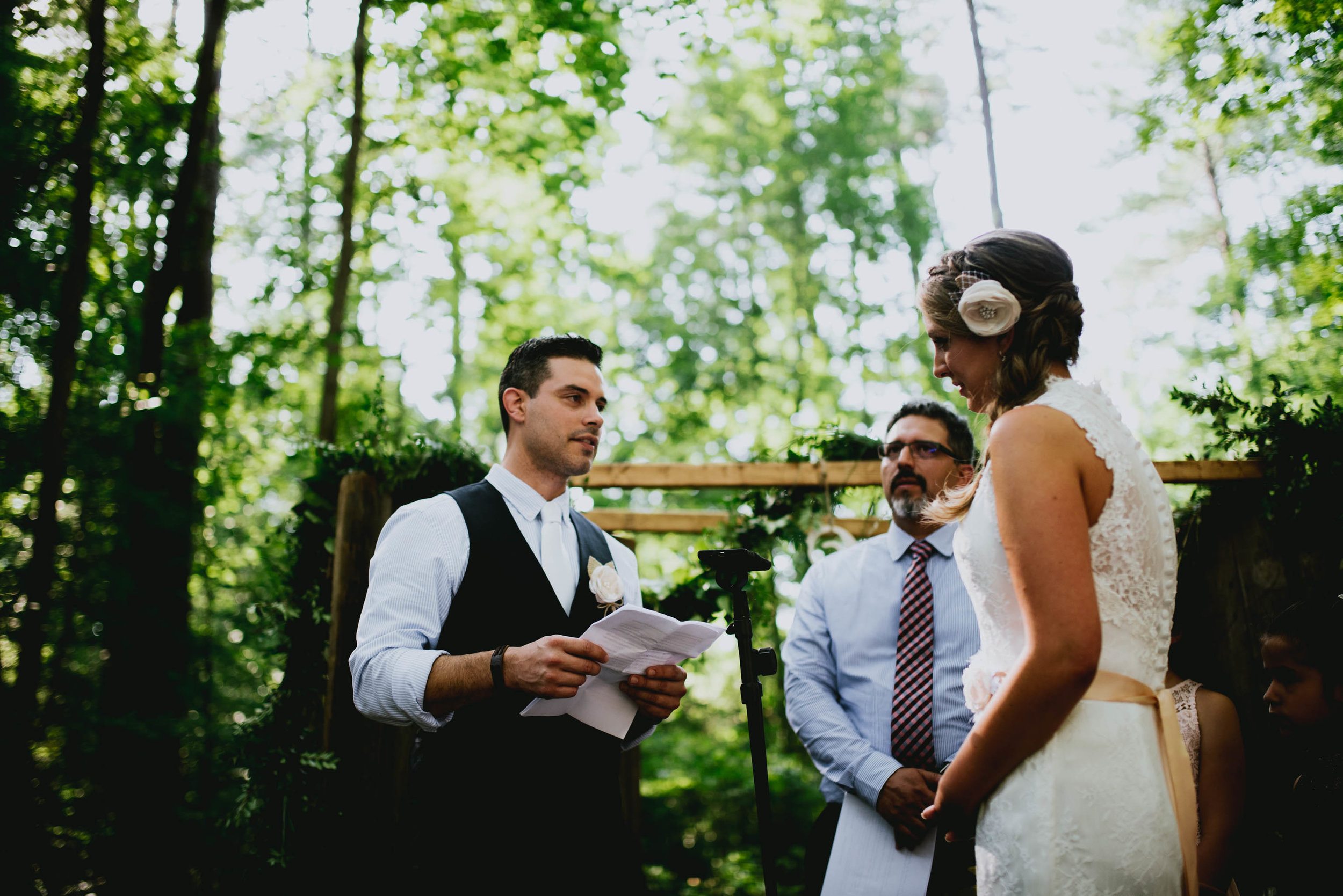 groom reading his vows to his bride during their wedding ceremony