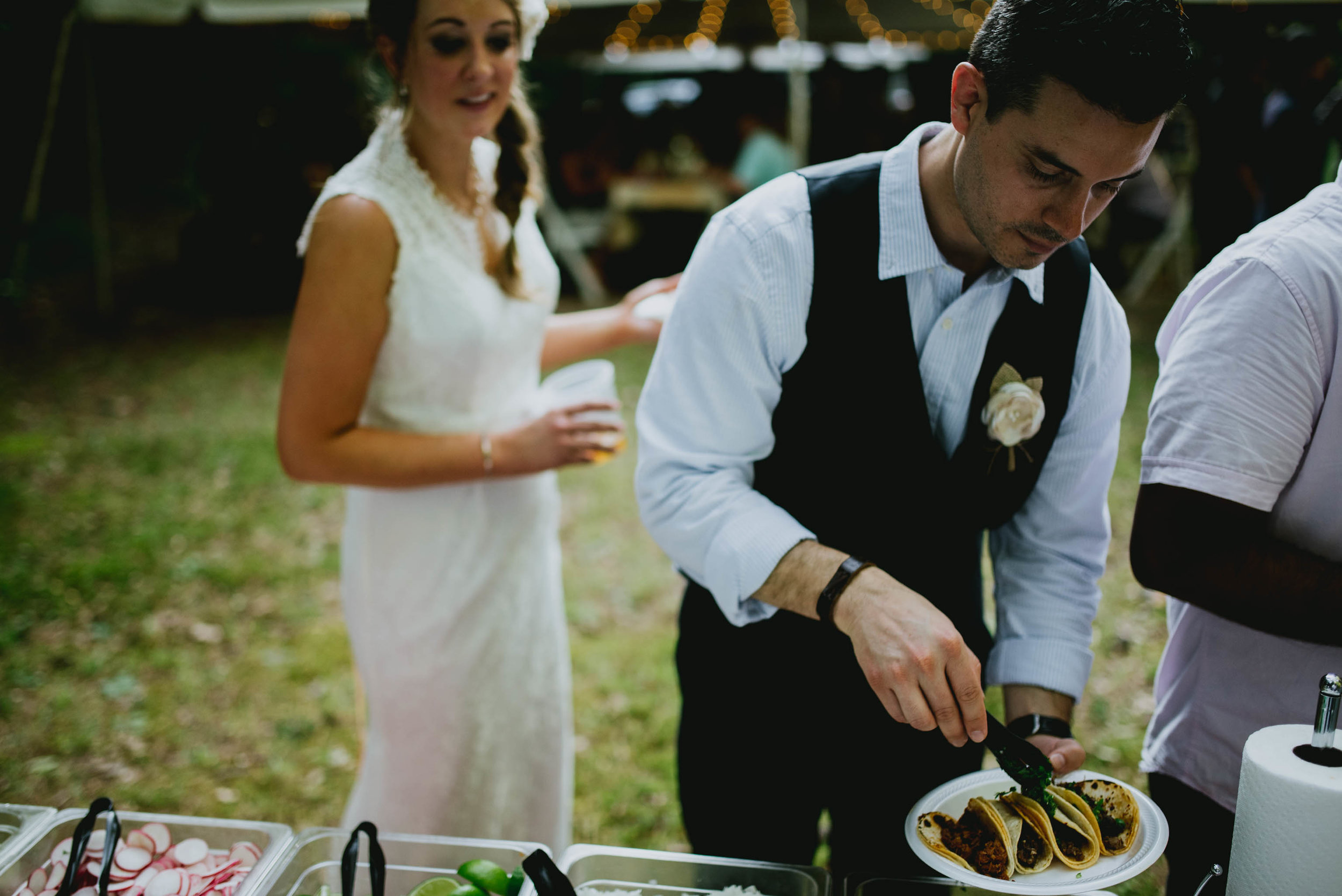 bride and groom getting their taco plates during their wedding reception